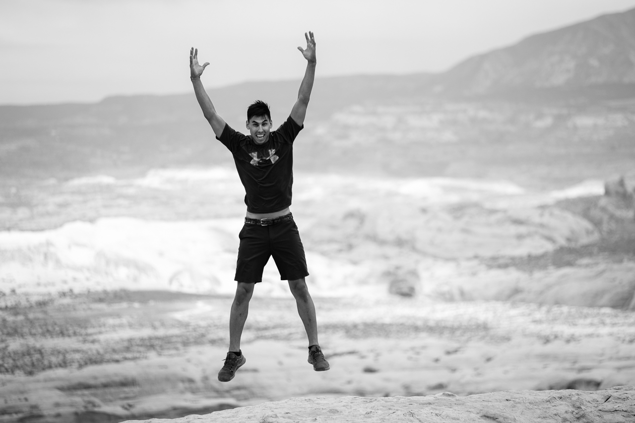 Day 222- 365 Day B&W Photo Challenge - Arin jumping for joy on the rocks inside the canyon. - Fuji X-T3, XF 50-140mm f/2.8, Acros  R Film Simulation