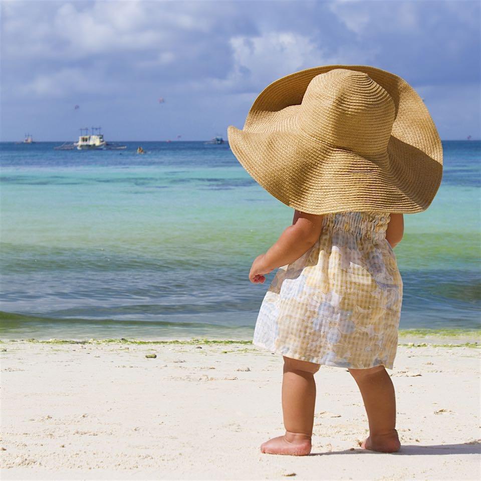 baby steht mit riesigem Hut am meer und staunt.jpg
