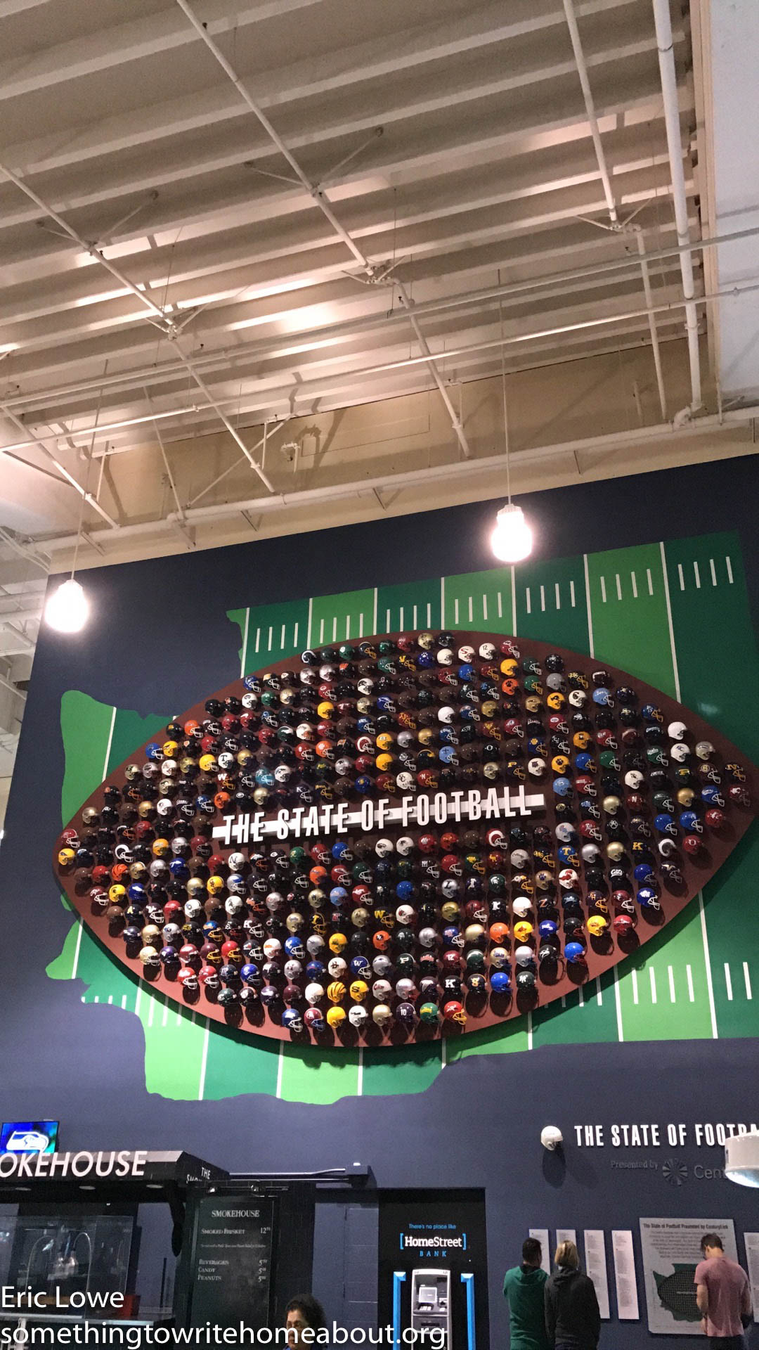 The State of Football. This piece features a depiction of Washington and holds replica football helmets from every high school football team in the state.