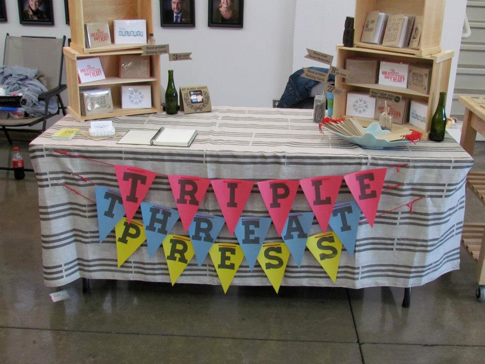 Our booth setup at our first handmade show. We had nine products. Our first sale was a Thug Life notebook.