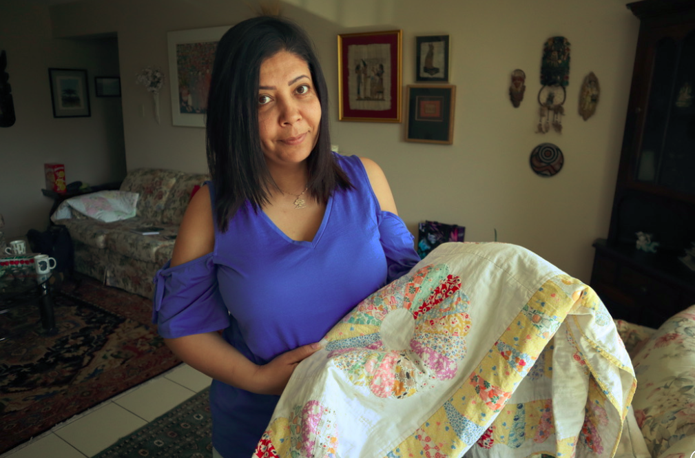 Siham holding the quilt given to her by one of her sponsors when she arrived in Canada.
