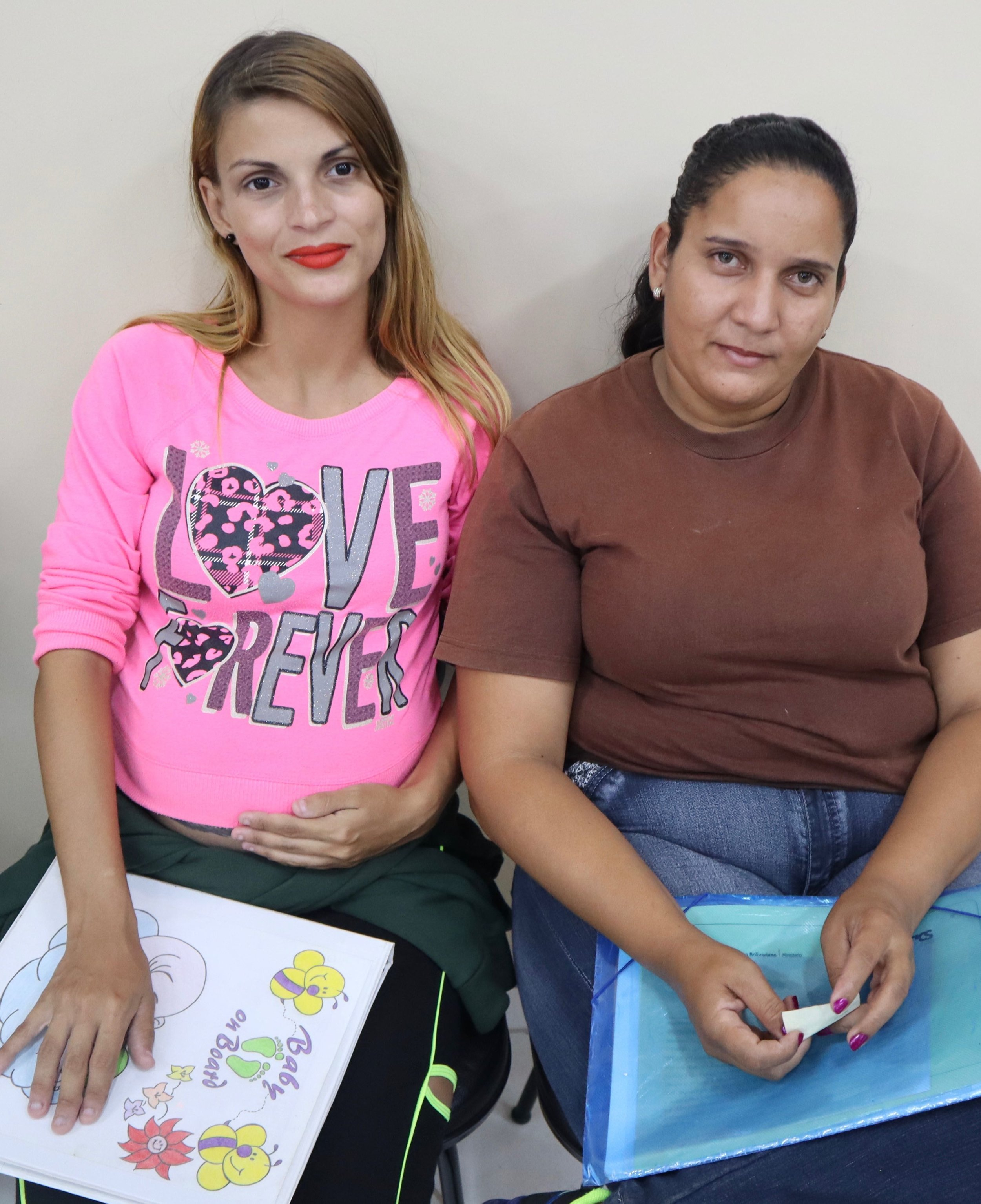 Mariana (left), holding a book for her soon-to-be-born baby