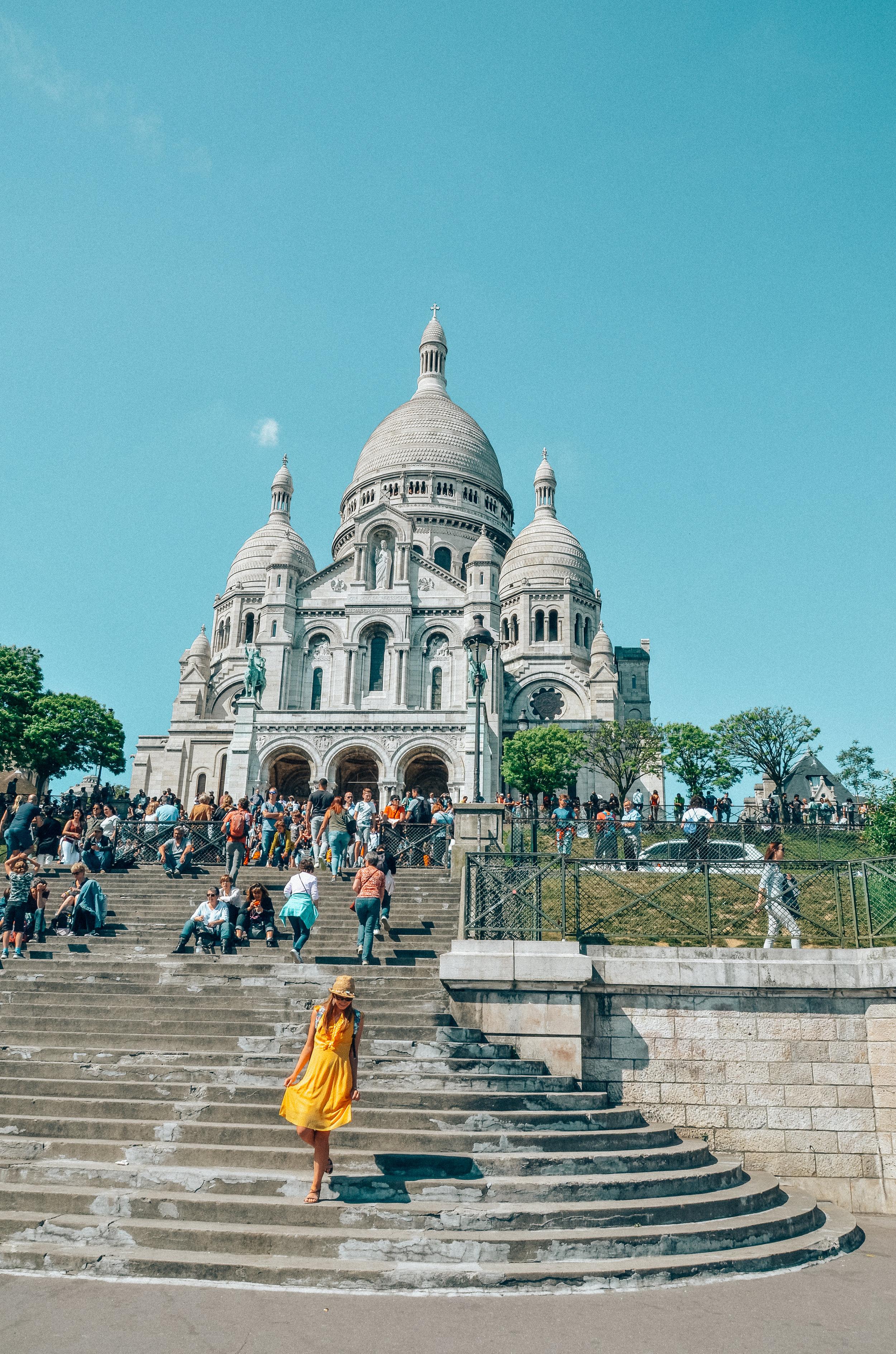 Eén van de allermooiste wijken van Parijs vind ik persoonlijk Montmartre. Montmartre is een hoge heuvel en een wijk in Parijs. Bovenop de heuvel staat de Basiliek de 'Sacre Coeur'. Bovenop de heuvel heb je een prachtig panoramisch uitzicht. Ik hou van de gezellige kleine steegjes, de gekleurde huisjes met groen begroeid, de kunstenaars die er portretten of karikaturen van je maken,... Alleen was het er net iets te druk, maar we waren er net op één van de drukste momenten van de dag. Zoals bij alle toeristische trekpleisters lijkt het me een goed idee om vroeg op te staan, dan zie je de plaatsen zonder de massa. Maar hé ik heb genoten van ons bezoekje aan Montmartre en uiteraard mocht 'La Maison Rose' niet ontbreken. Dat prachtige roze caféetje met de sierlijke letters. We wandelden iets verder, de grote drukte uit en we dronken iets op een gezellig terrasje. Want dat is ook Parijs. De kleine steegjes en pleintjes, achter de hoek van de toeristische trekpleisters, die vaak onverwacht ook héél erg gezellig blijken te zijn.  I personally think that Montmartre is one of the most beautiful places in Paris. Montmartre is a high hill and a neighborhood in Paris. On top of the hill one can find the Basilica the Sacre Coeur. On top of the hill you have a beautiful panoramic view. I love the cozy little alleys, the colored houses with greenery, the artists who make portraits or caricatures of you, ... Only it was just a little too crowdy, but we were there just at one of the busiest times of the day. As with all tourist attractions it seems like a good idea to get up early, then you see the places without the crowd. But hey I enjoyed our visit to Montmartre and of course 'La Maison Rose' had to be on our list! That beautiful pink cafe with the ornate letters. We walked a little further, away from the the big crowds and we drank something on a cozy terrace. Because that is also Paris. The small alleys and squares, behind the corner of the tourist attractions, which often unexp
