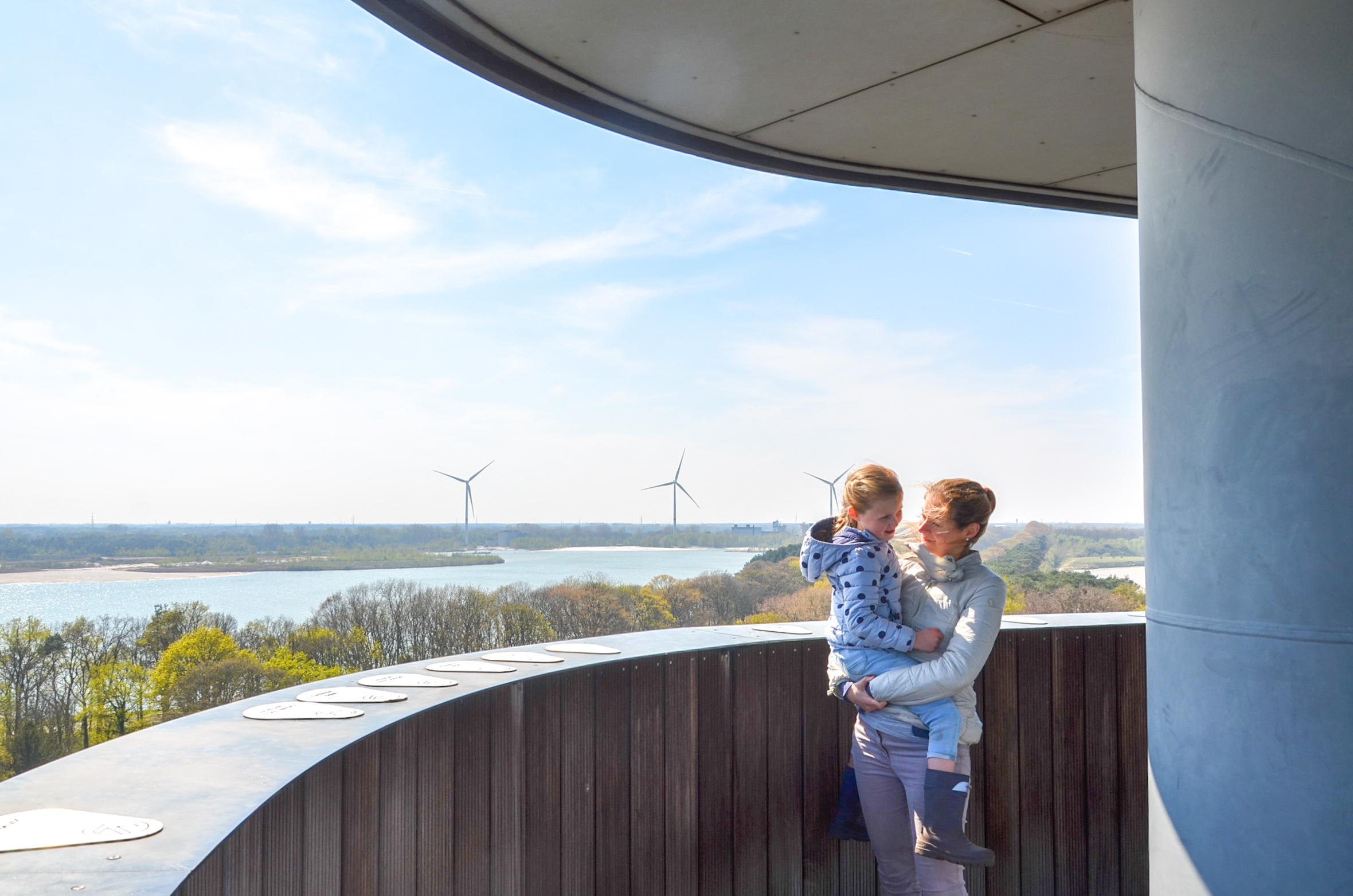 Wapperende haren door de felle wind boven op de Sas-4-toren in Dessel, maar wat een uitzicht