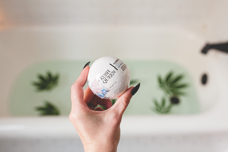 Model holding white Shield 100mg Immunity Bath Bomb in front of tub with clear water and floating hemp leaves.