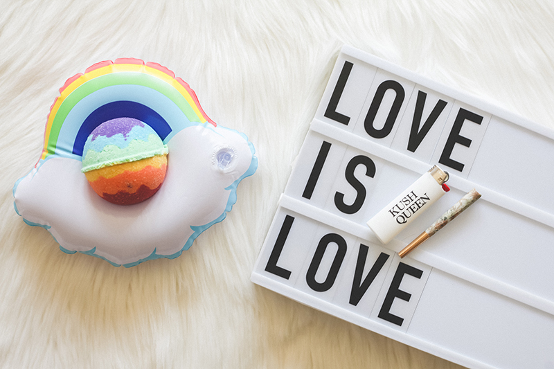 Rainbow Pride CBD Bath Bomb by Kush Queen featured on mini Rainbow floaty next to sign reading Love is Love.