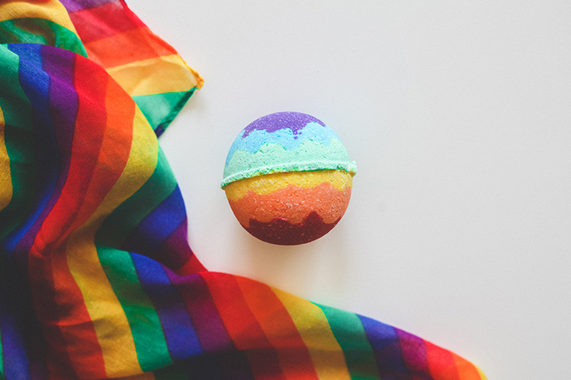 CBD Pride 2019 bath bomb featured near rainbow Pride flag.