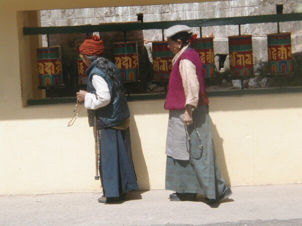 Two Buddhists turning traditional prayer wheels, near Dharamshala.