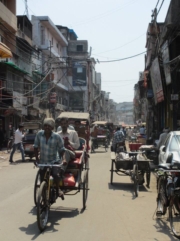 An old fashioned rickshaw on a typically busy street in Old Dehli.