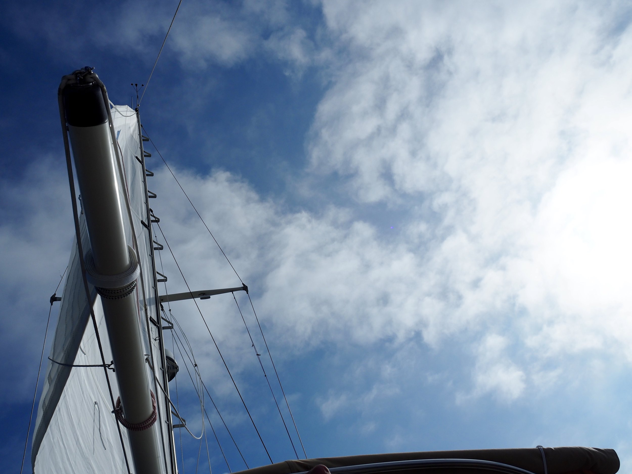 The peace of a full sail and a blue sky. Also of a boat so well balanced — even close hauled — you can lie back in the cockpit and see the world this way.