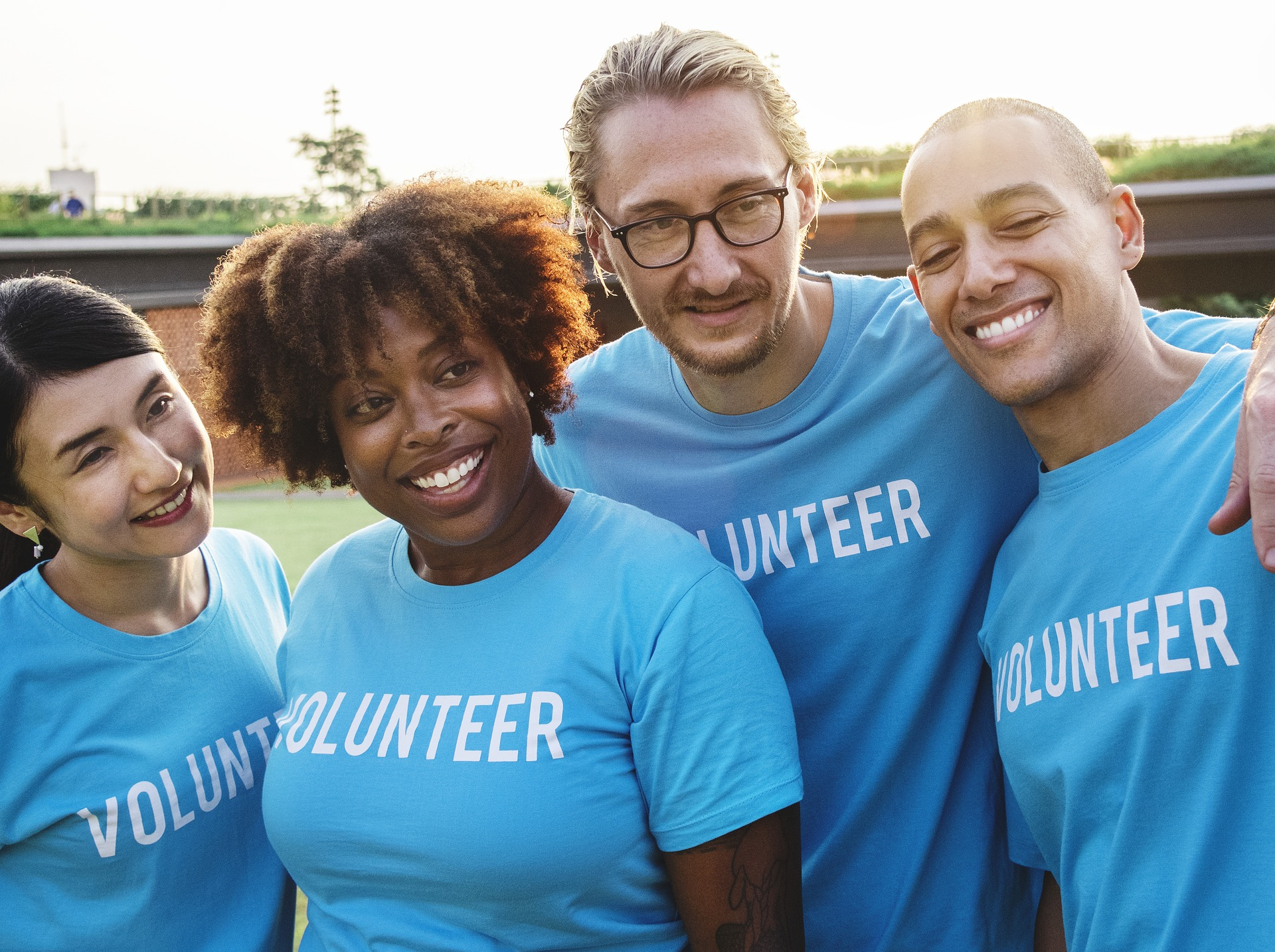 Find one volunteering opportunity. Pictured: Four people with 'volunteer' shirts.