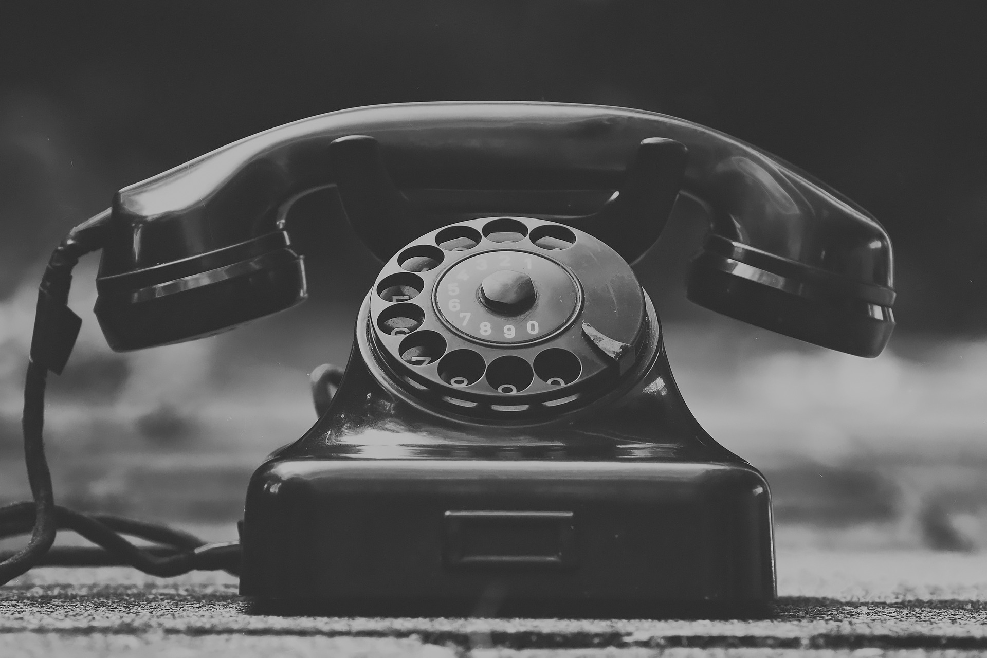 Call a loved one once a week. Pictured: Black and white photo of old landline phone.