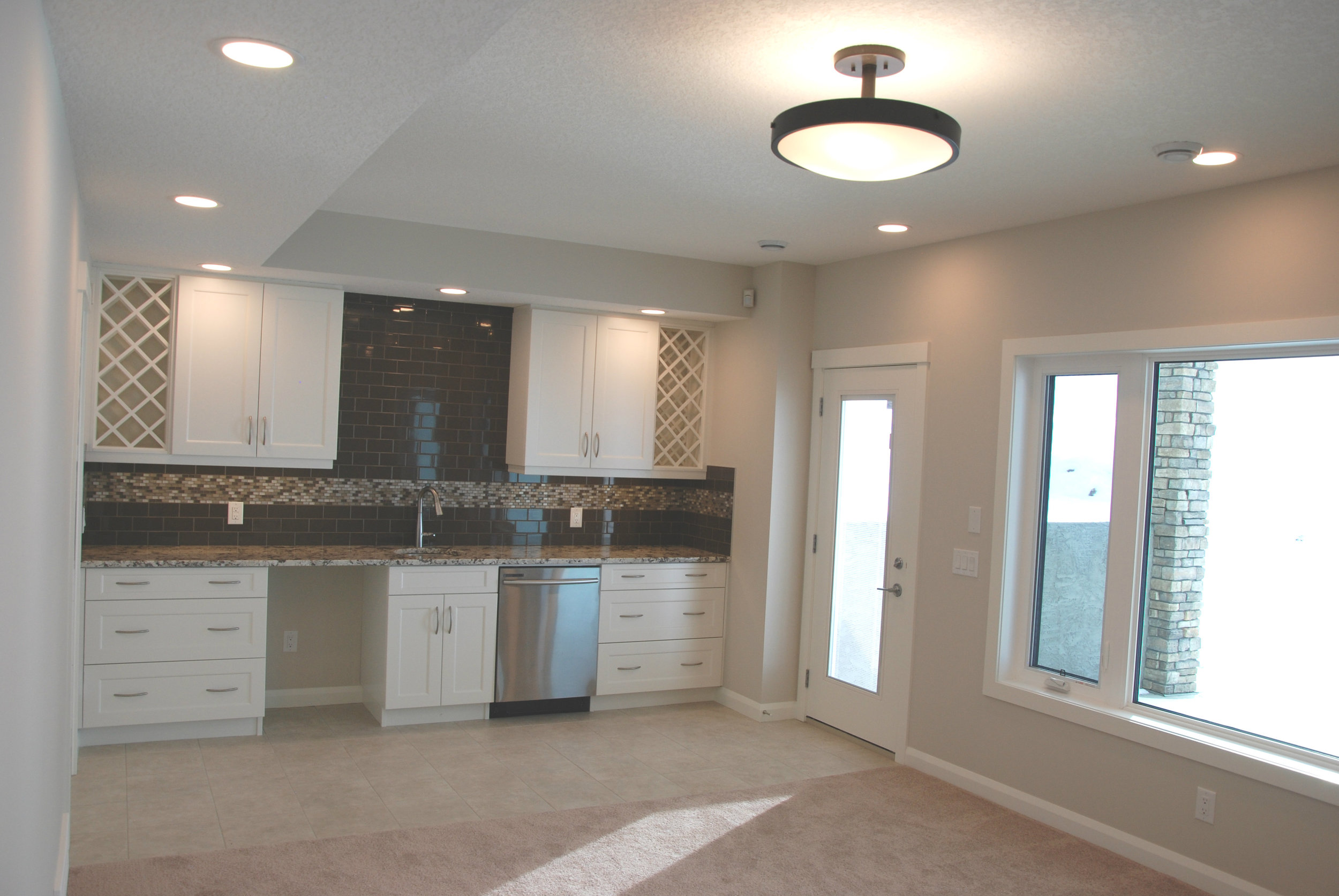 The generous downstairs entertaining area features a tiled backsplash and bar area as well as access to the west facing covered deck.