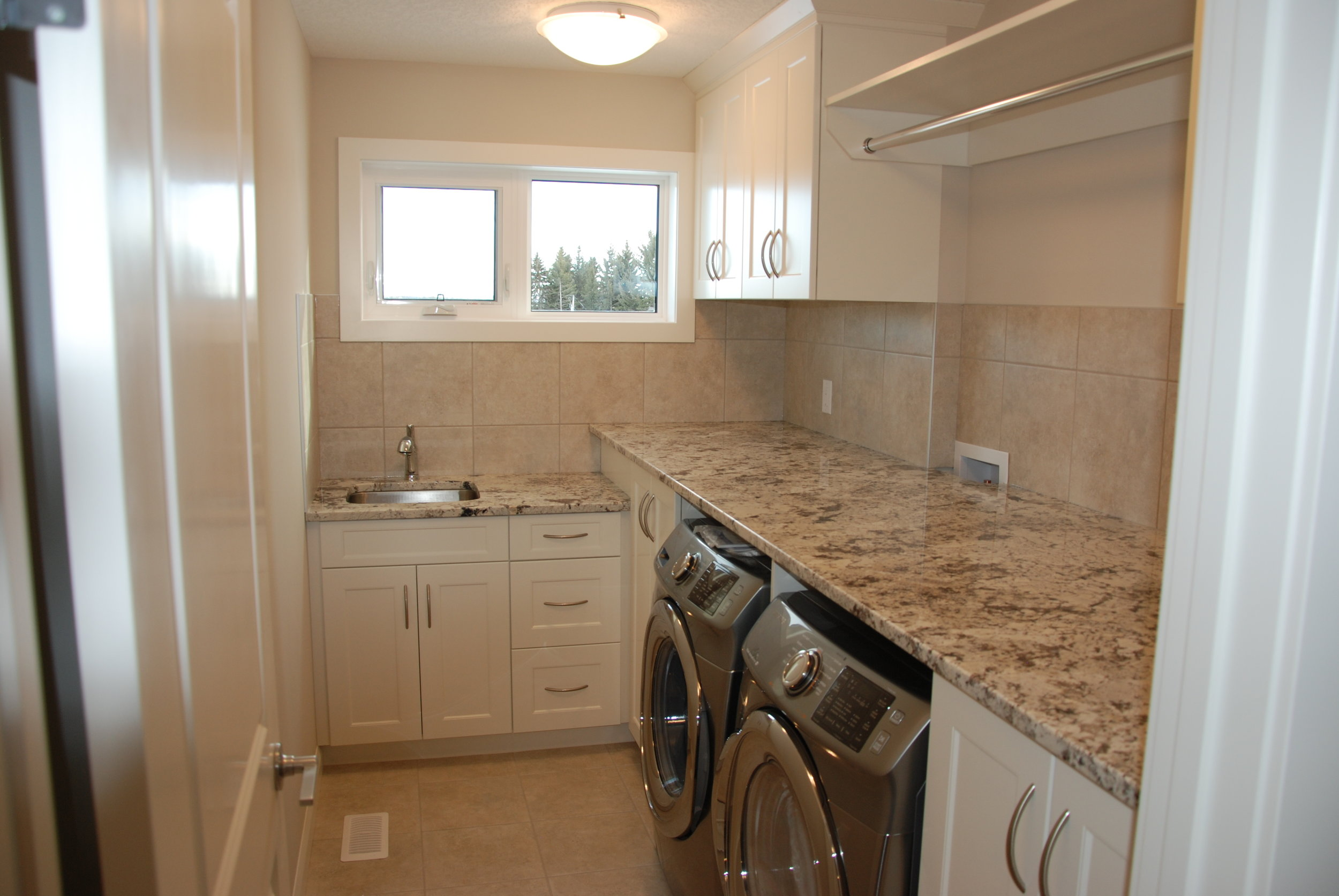 Convenient upstairs laundry is well appointed. A sink, storage space and hanging area are all surrounded by Italian ceramic tile.