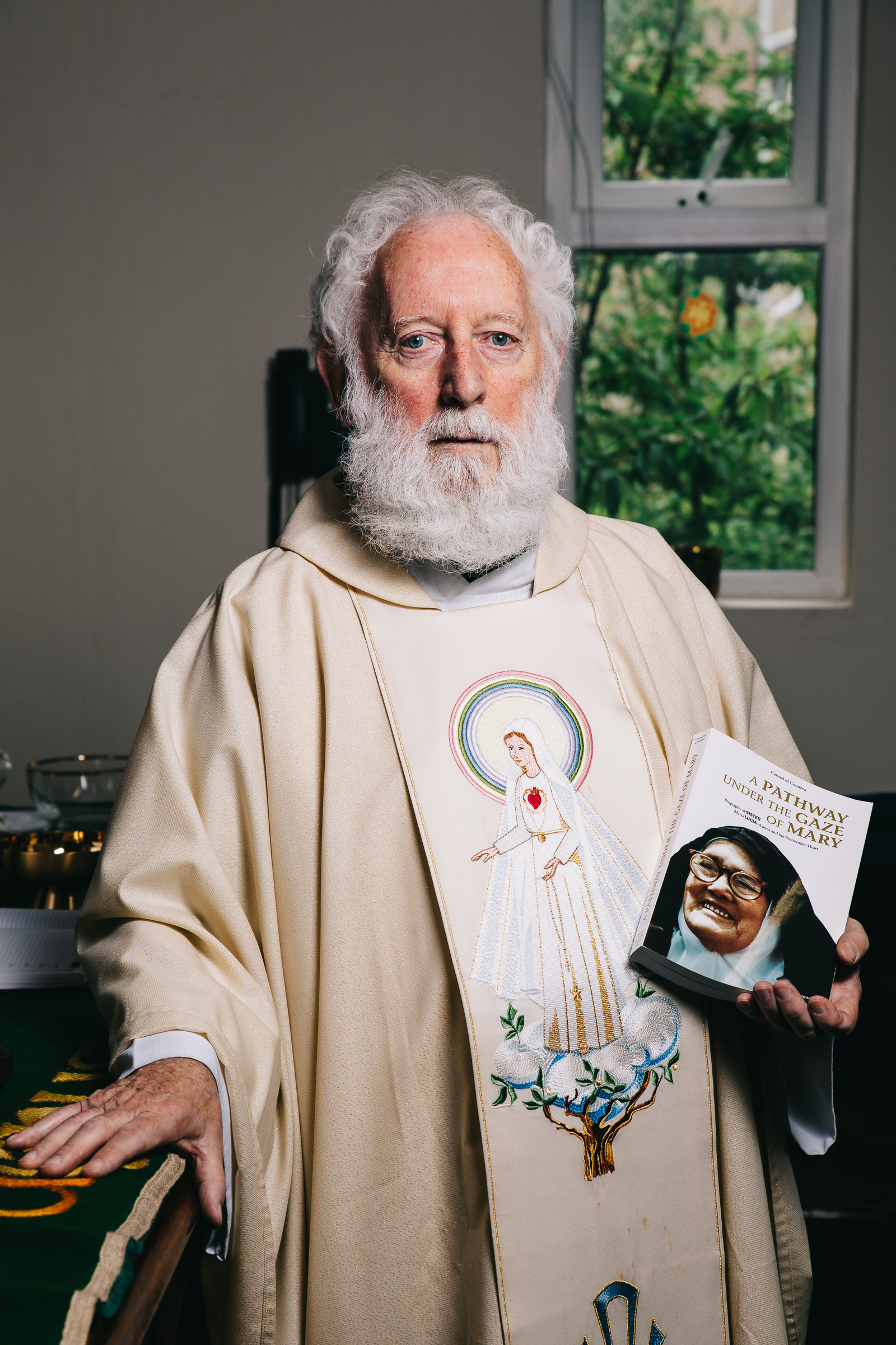 Dressed To Praise - Robed with vestments of Our Lady Of Fatima that he got 10 years ago in Portugal, Fr.Maher turns and shows me the book, a biography of Lucia. It's the latest most popular book doing the rounds and so it stays with him at all times.
