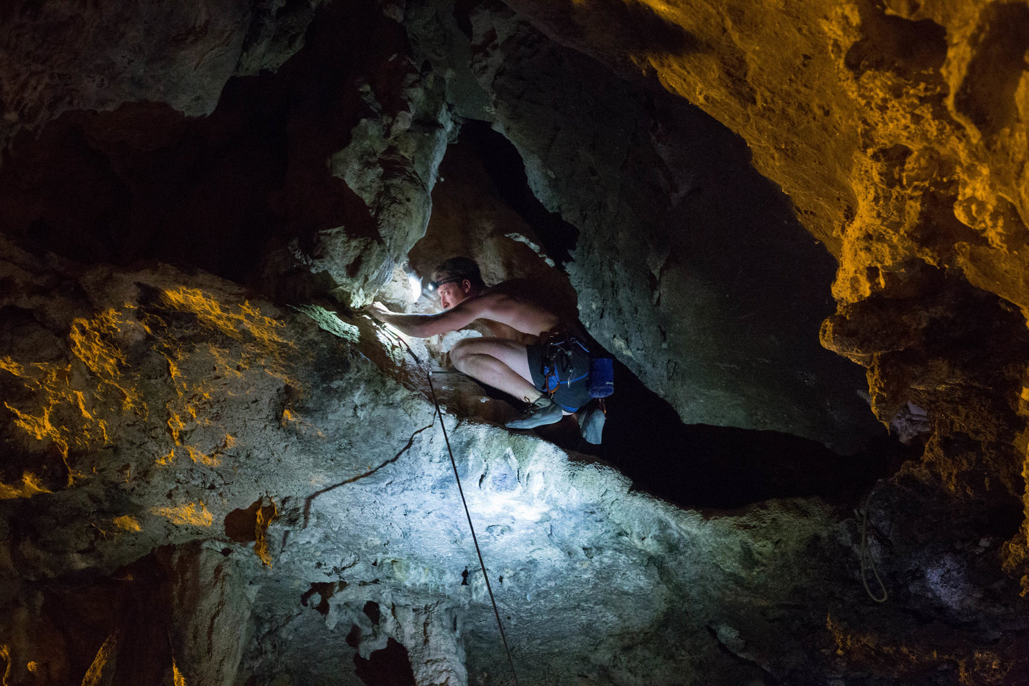 Climbers use headlamps to guide their way across narrow ledges and caves after sundown on Tonsai Beach in Thailand. March 2017.