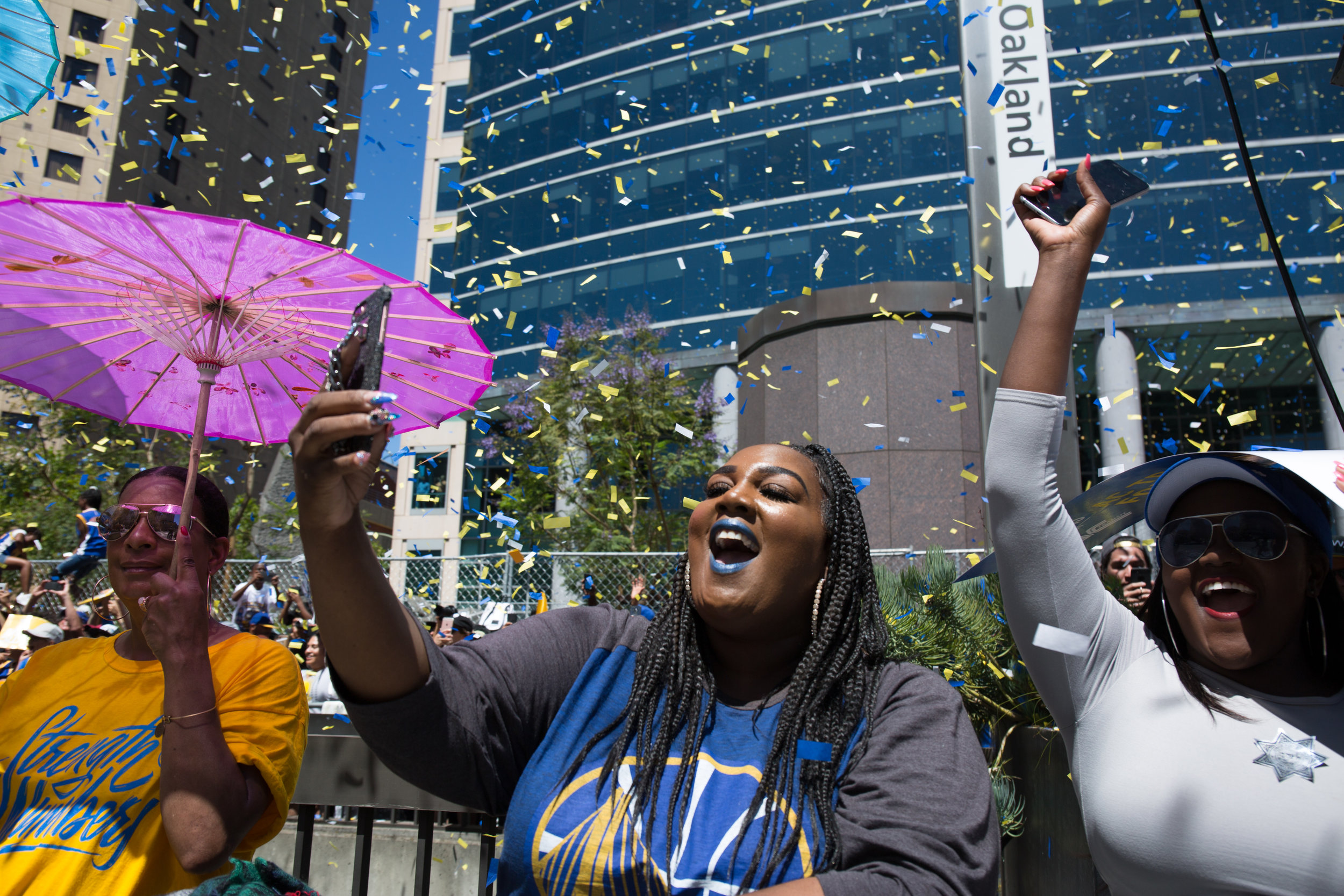 Amelia Johnson, 27, center, cheers as a tour bus carrying Steph Curry, his wife, Ayesha, and their daughter, Riley, passes by at the 2018 Warriors Championship Parade in Oakland, CA on June 12, 2018.