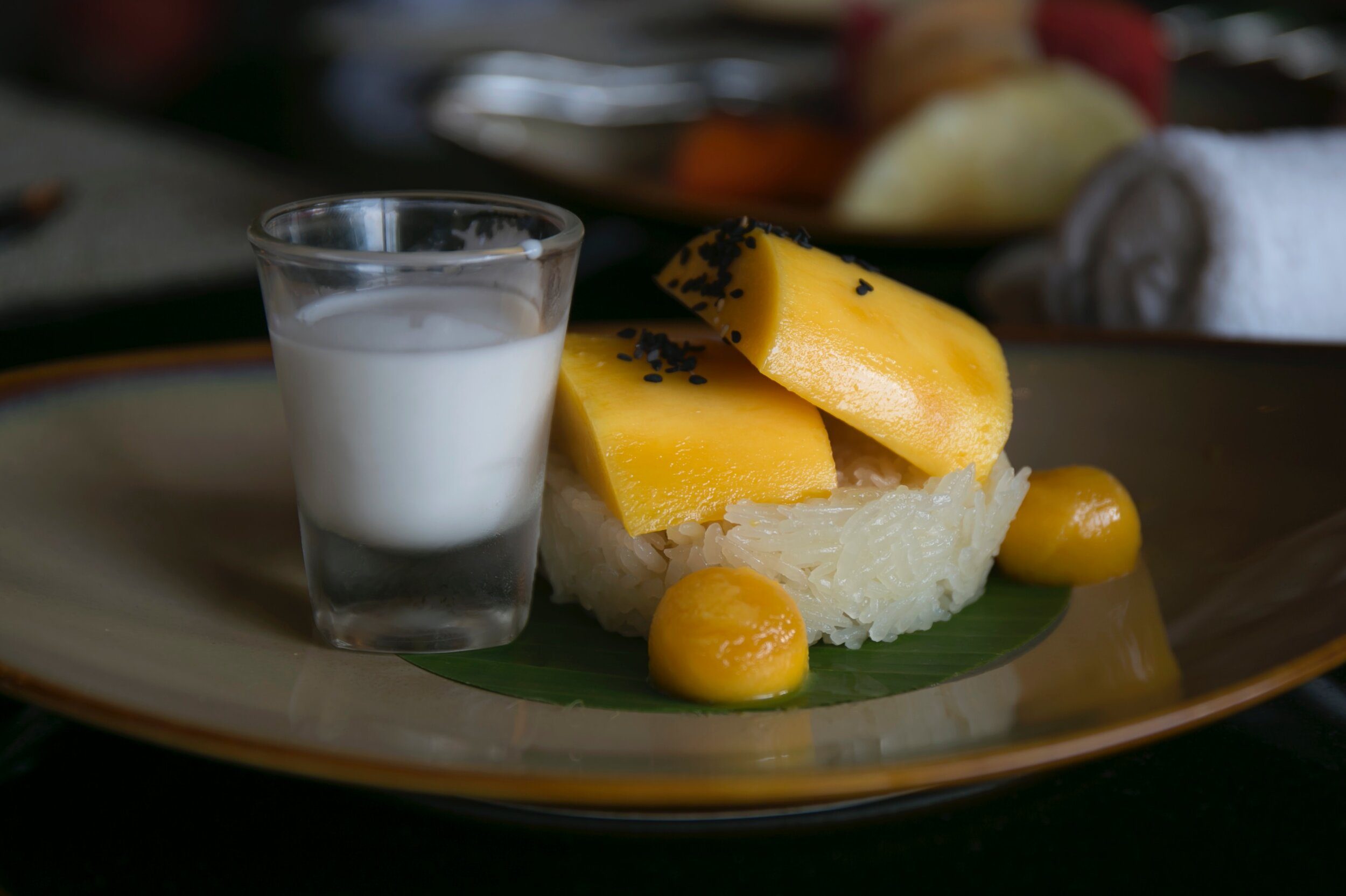 Typical Thai dessert: sticky rice with mango and COCONUT milk on the side.  Image source:  Unsplash .