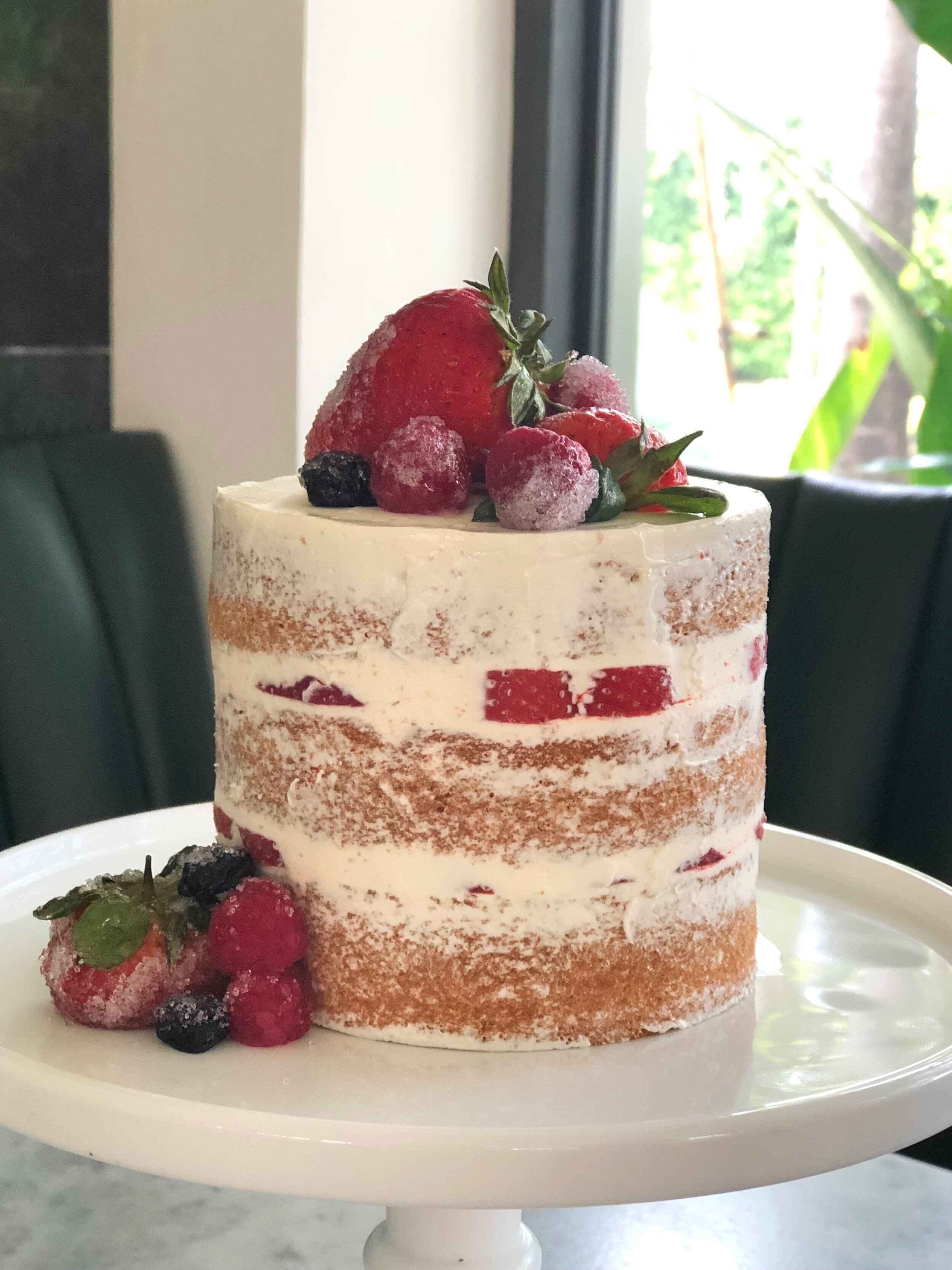 Our #6 Naked Cake with strawberries and blueberries, buttercream icing.
