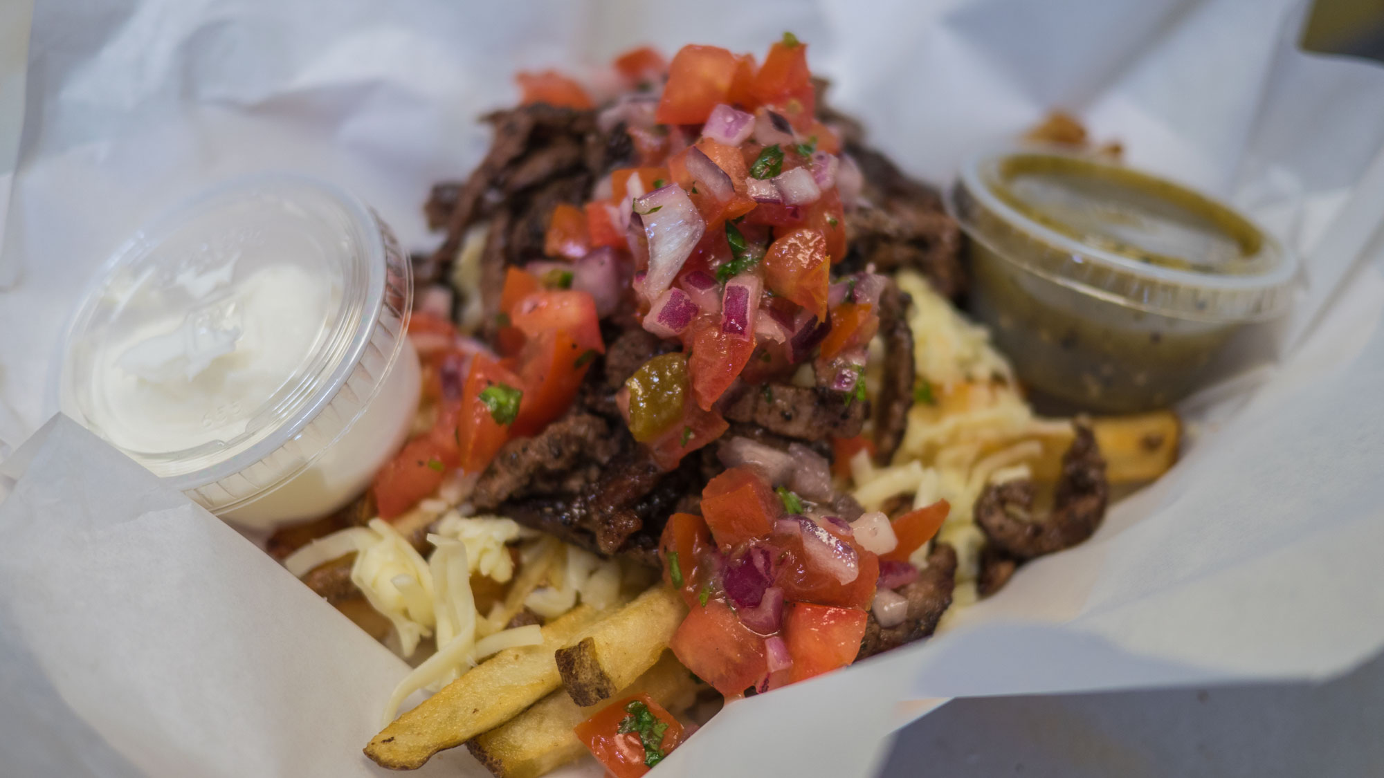 CARNE ASADA FRIES - Grilled beef with pico de gallo, Monterey jack cheese, salsa verde, sour cream over fresh cut fries.