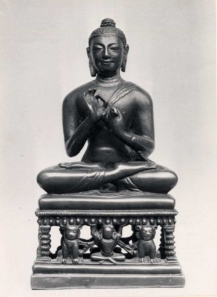A gilded bronze figure of the Buddha seated on a throne supported by lions.  8th C