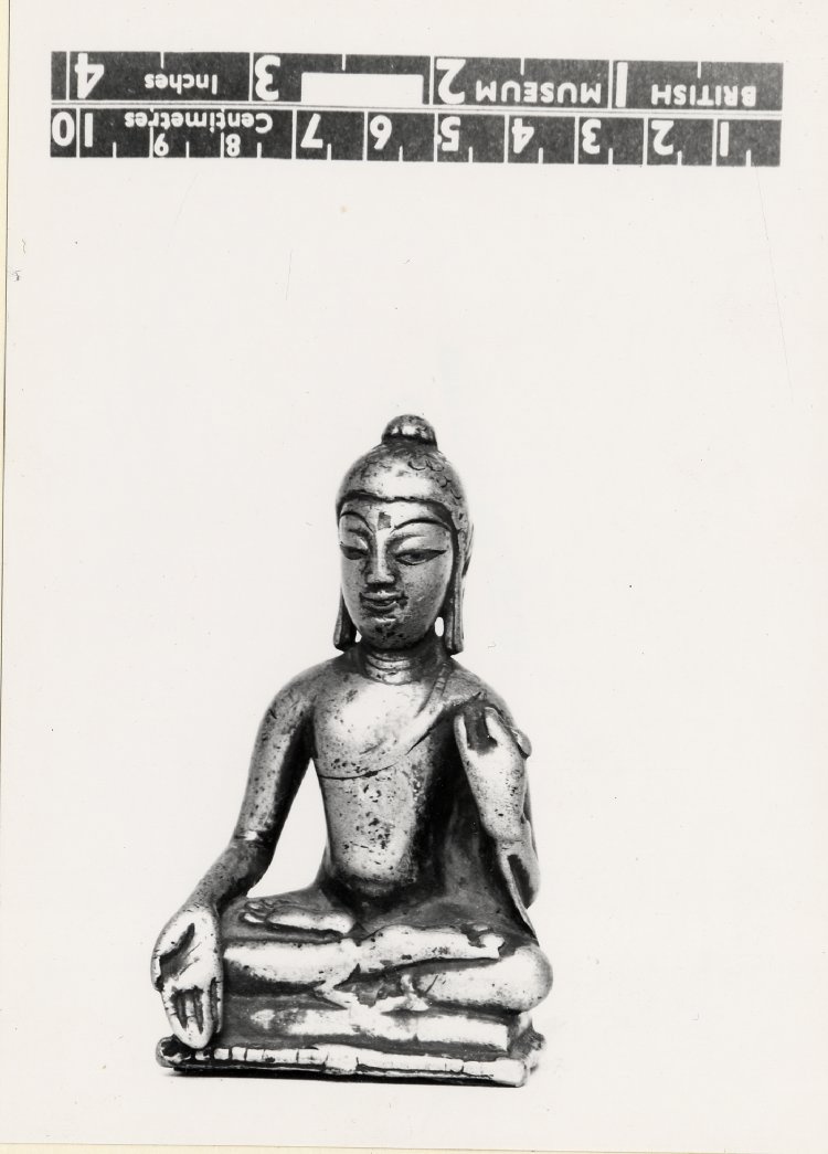 Seated figure of the Buddha, with right hand in varadamudrā and left raised by the shoulder holding his garment end; cast in a copper alloy with silver inlay. Thin copper base plate; inscribed on the rear. 9th C - 11 th C