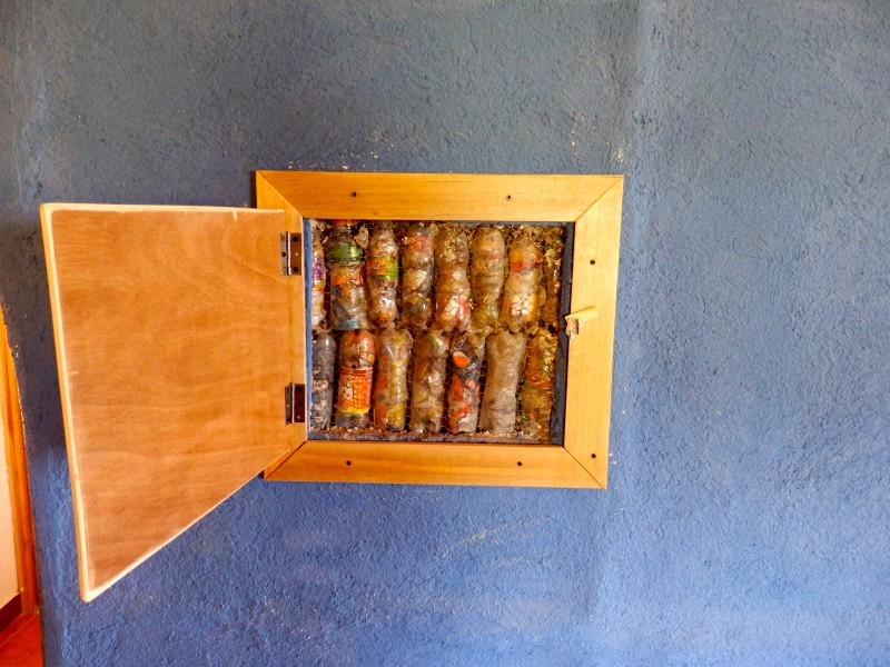 A panel in the interior wall of the house, revealing what the walls are made of—ecobricks made from recycled soda bottles.