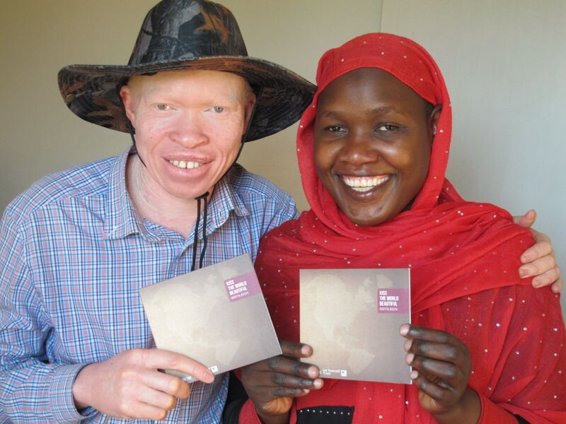 """Peter & Fazira, a vital part of Advantage Africa's team on the ground in Uganda, hold their copies of Martyn Joseph's """"Kiss the World Beautiful""""."""