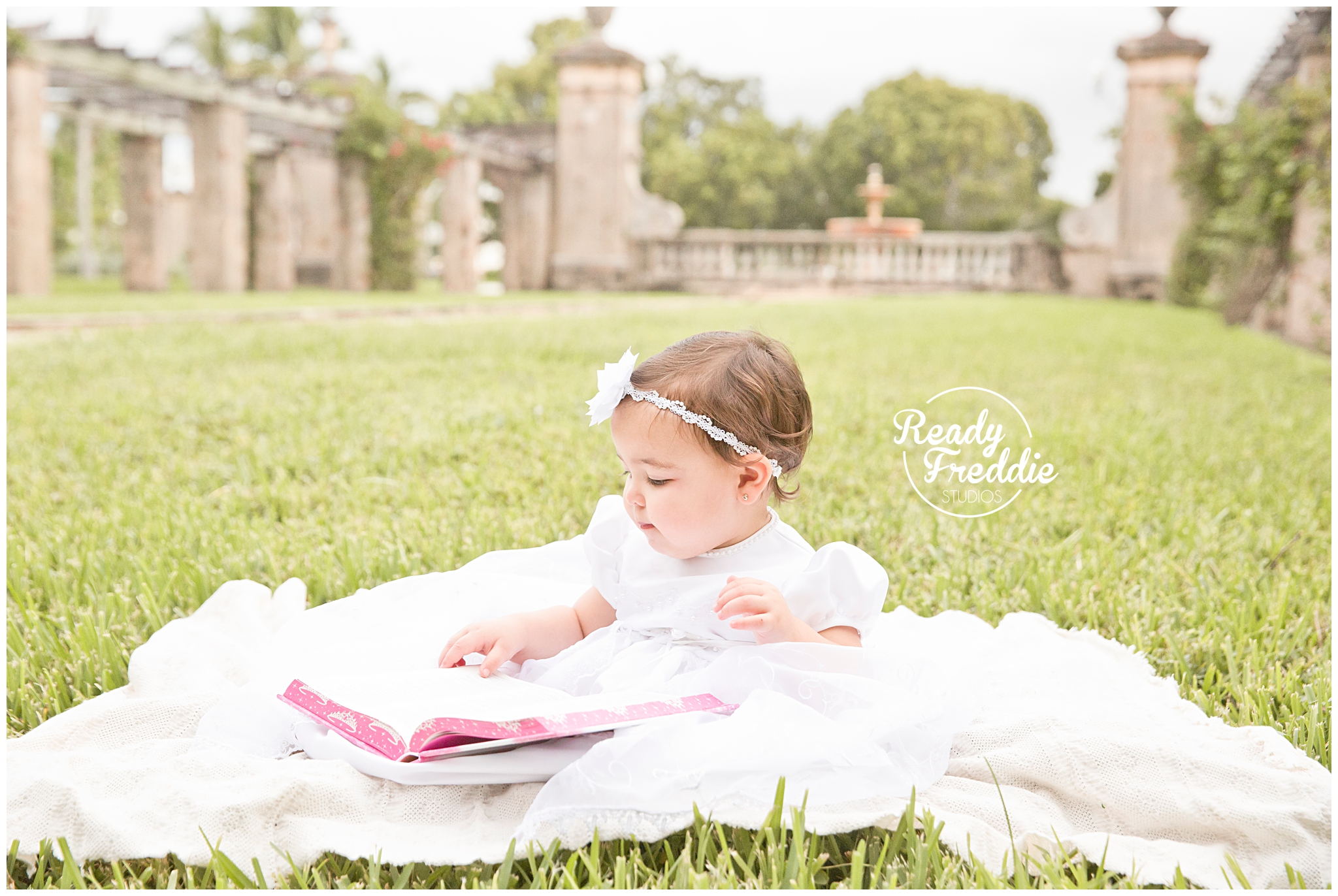 Little girl sitting down in her baptism gown reading a bible