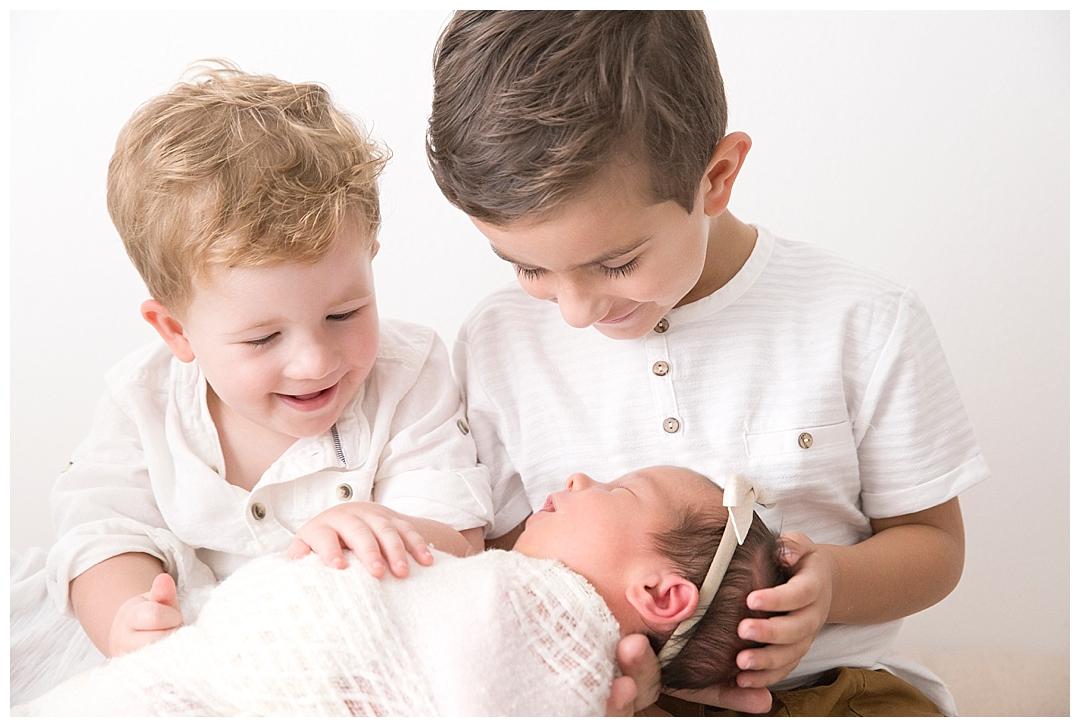 boys holding newborn sister | miami newborn photographer