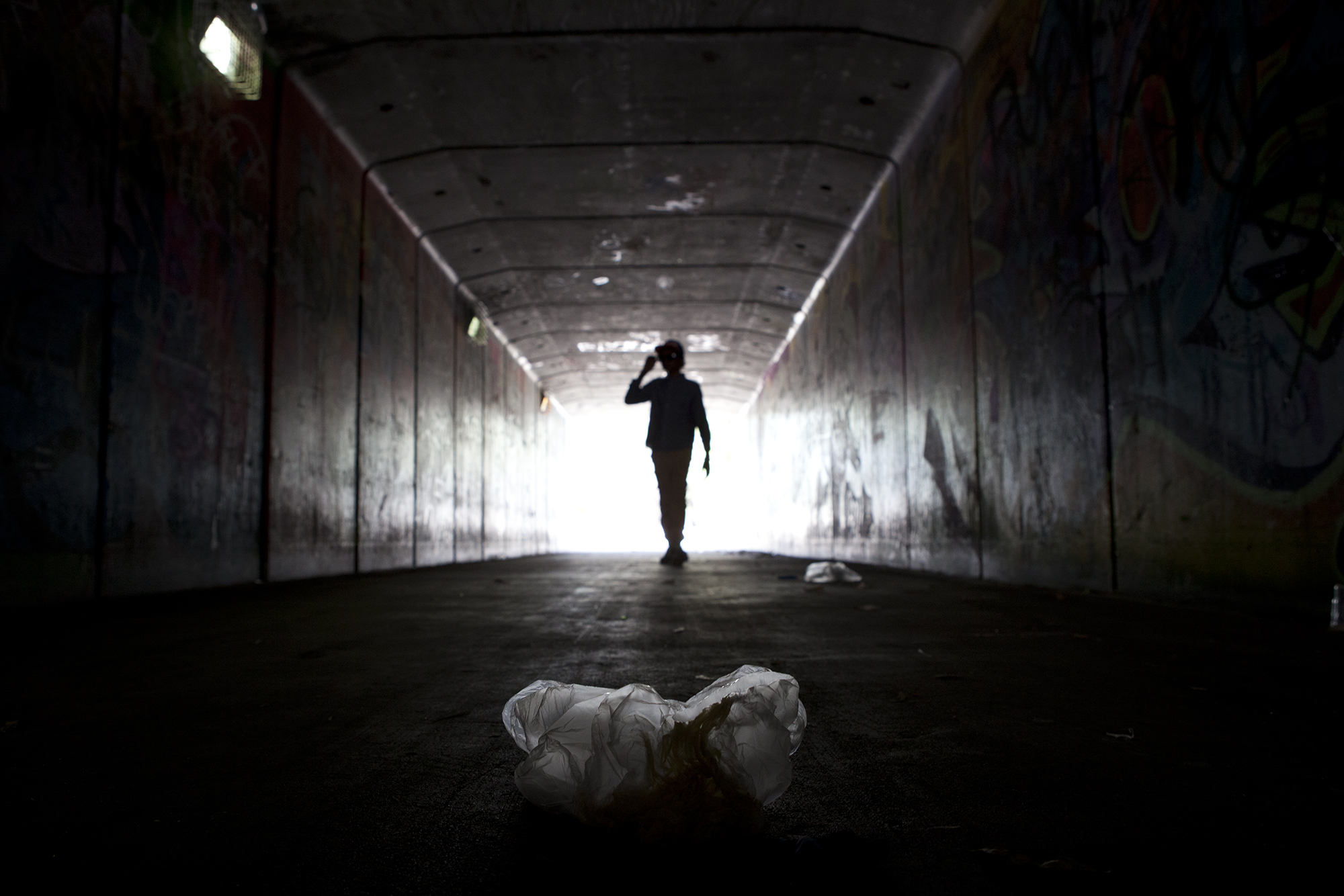 A dark tunnel on the outskirts of Rockhampton, littered with scrunched up plastic bags which have been filled with glue or paint used for sniffing.