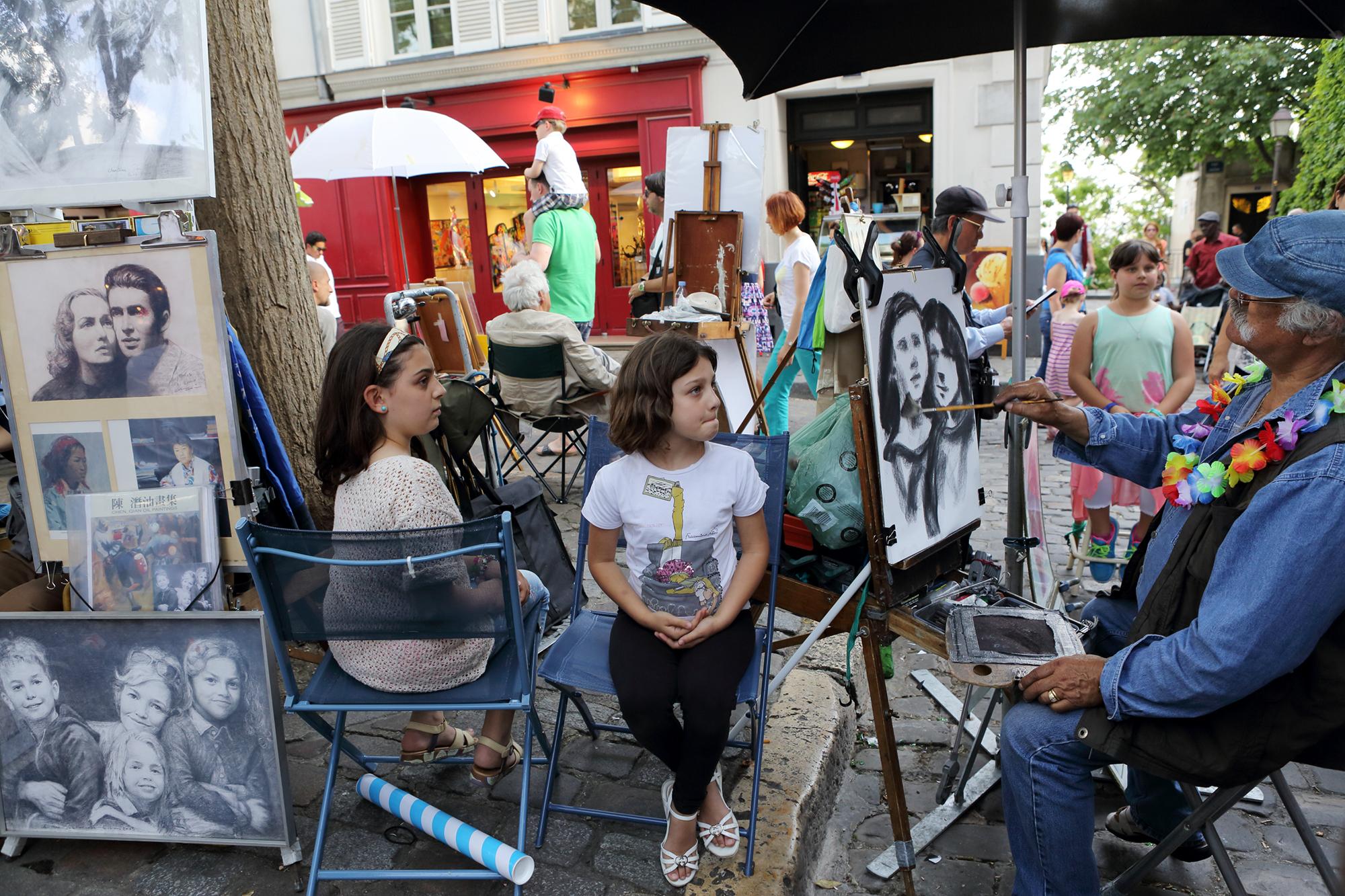 Sitting for a portrait in Montmartre, Paris.