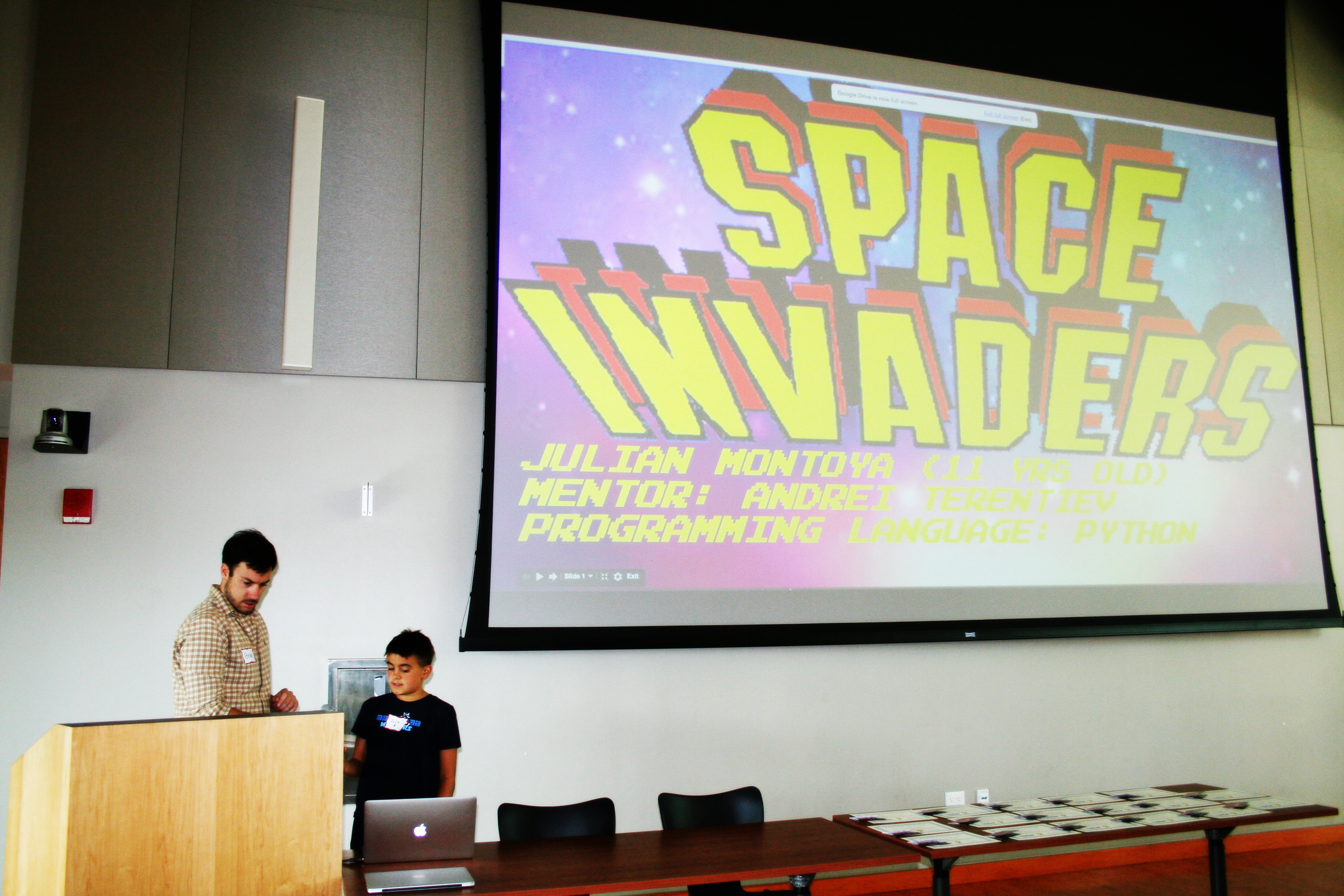 Brian Skinner with Julian Montoya, presenting his Space Invaders game