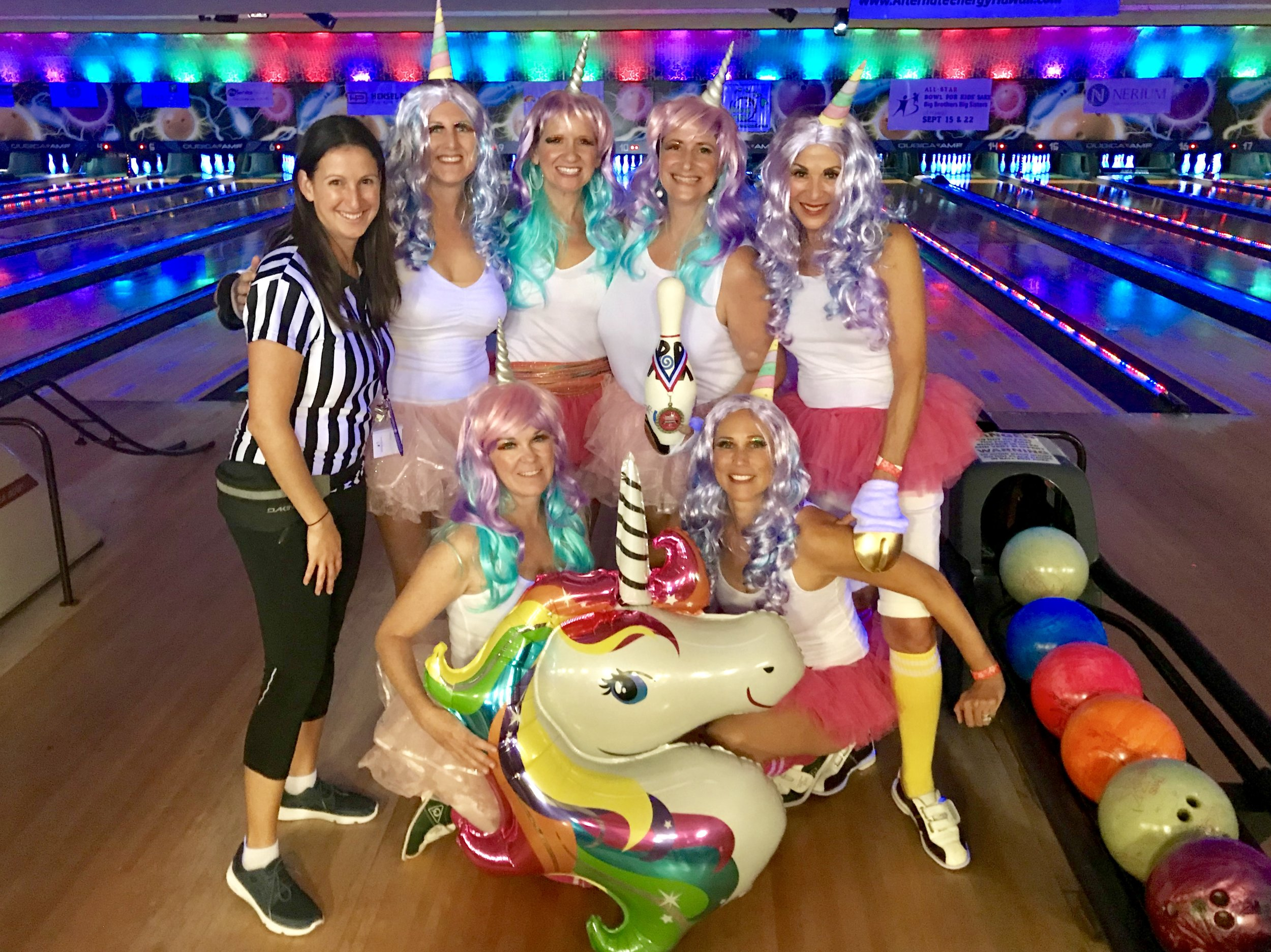 Mandy Trella of Big Brothers Big Sisters (left-Referee)  joins Monica Lau Photography (top row center-holding bowling pin) and the herd of Unicorns. Gina Loose, Gina Cargile, Marilee Mattson, Courtney Sibley, and Melissa Bruhl.