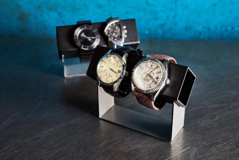 """WATCH HOLDER   腕時計コレクターにのリクエストに応えて製作したウォッチスタンド。デザインが気に入って手に入れた大切な腕時計も、寝かして並べておいては眺めて楽しむことが出来ません。このウォッチスタンドがあれば腕時計の""""見せる収納""""が可能です。  上下パーツは取り外し式。時計本体が直接触れる上部は、磁石類に影響しないようアルミ素材で製作しました。落ち着きのあるマットブラックと、インダストリアルなシルバーのコンビネーションが、大切な腕時計のデザインを際立たせます。高さの違う(S)(M)の2サイズを、前後に並べてディスプレイをお楽しみください。"""
