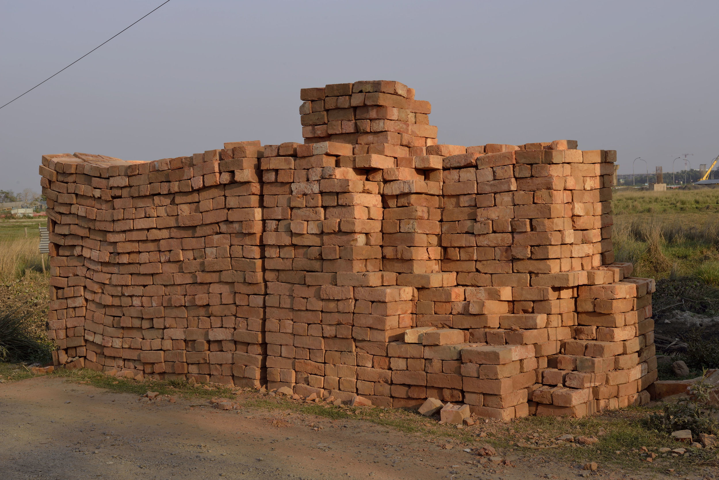 """Bricks on the Outskirts of Kolkata, India  The use of bricks as a building material goes back at least 9,500 years as confirmed at a site in Tell Aswad in the upper Tigris region of what is now modern Syria.  In the Old Testament in Exodus 1:14; 5:4-19 we are told that the Egyptians """"came to dread the Israelites and worked them ruthlessly. They made their lives bitter with harsh labor in bricks and mortar.""""   The organization Union Solidarity International has been campaigning against """"blood bricks"""" in India since 2012. In the words of Andrew Brody, """"its modern day slavery. Entire families of men, women, and children are working for a pittance, up to 16 hours a day in terrible conditions. There are horrific abuses of minimum wage rates and health and safety regulations, and it's often bonded labor, so they can't escape."""""""