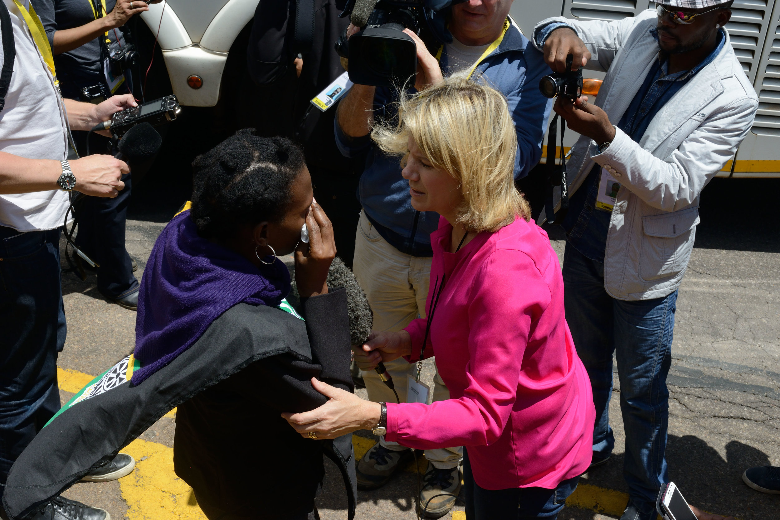 "An anchorwoman interviewing a mourner who has just viewed the body of Nelson Mandela lying in state, Pretoria, South Africa  At the Rivonia Trial, in which he and his comrades were sentenced to life in prison on Robben Island for committing high treason, Nelson Mandela defiantly claimed, ""I have cherished the ideal of a democratic and free society in which all persons live together in harmony and with equal opportunities. It is an ideal, which I hope to live for and to achieve. But if needs be, it is an ideal for which I am prepared to die.""  Born into a royal family of the Thembu tribe, Mandela spent his boyhood herding sheep and goats.  He lived to become the first black president of South Africa, a Nobel Prize winner, and a deeply revered figure throughout the world.   When Mandela visited the United States in 2008 he was required to obtain special State Department clearance because his name remained on the U.S. Terrorism watchlist."