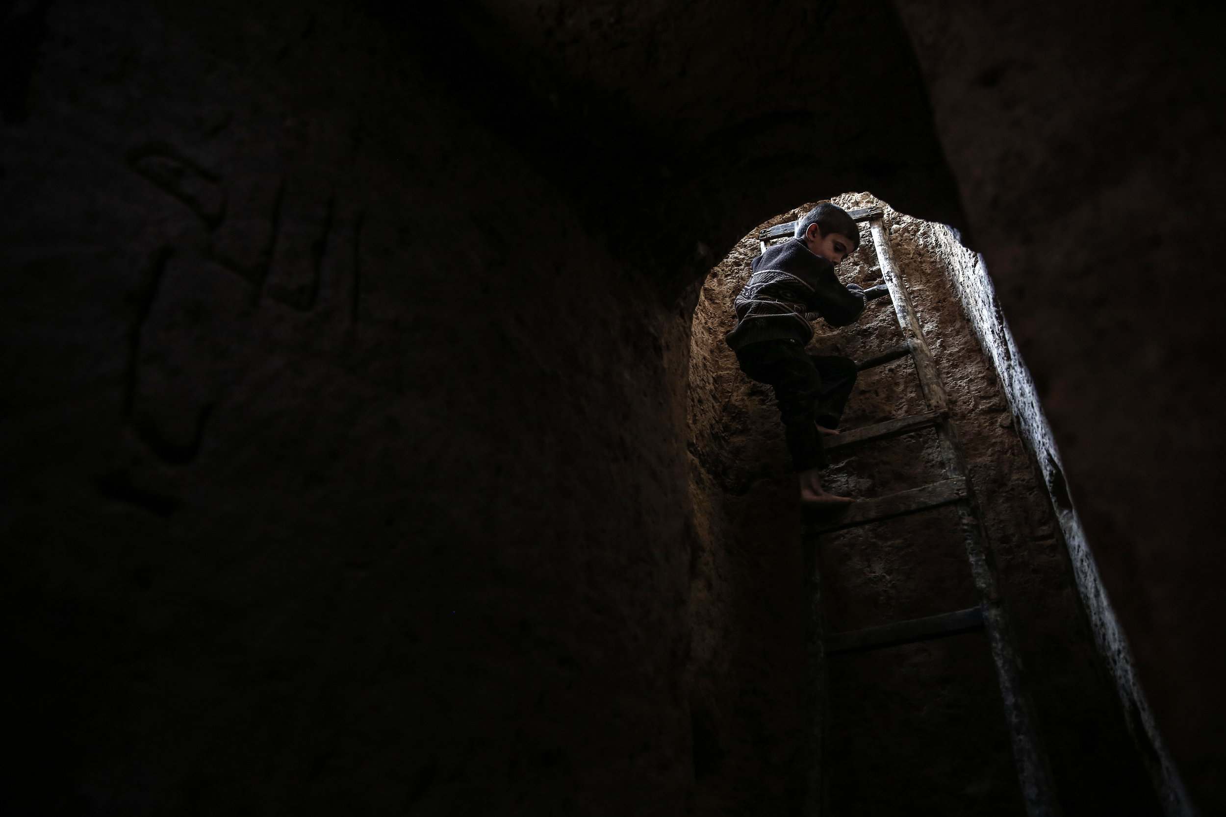 - A boy climbs into Abu Omar's shelter in the city of Douma, on the eastern outskirts of Damascus.
