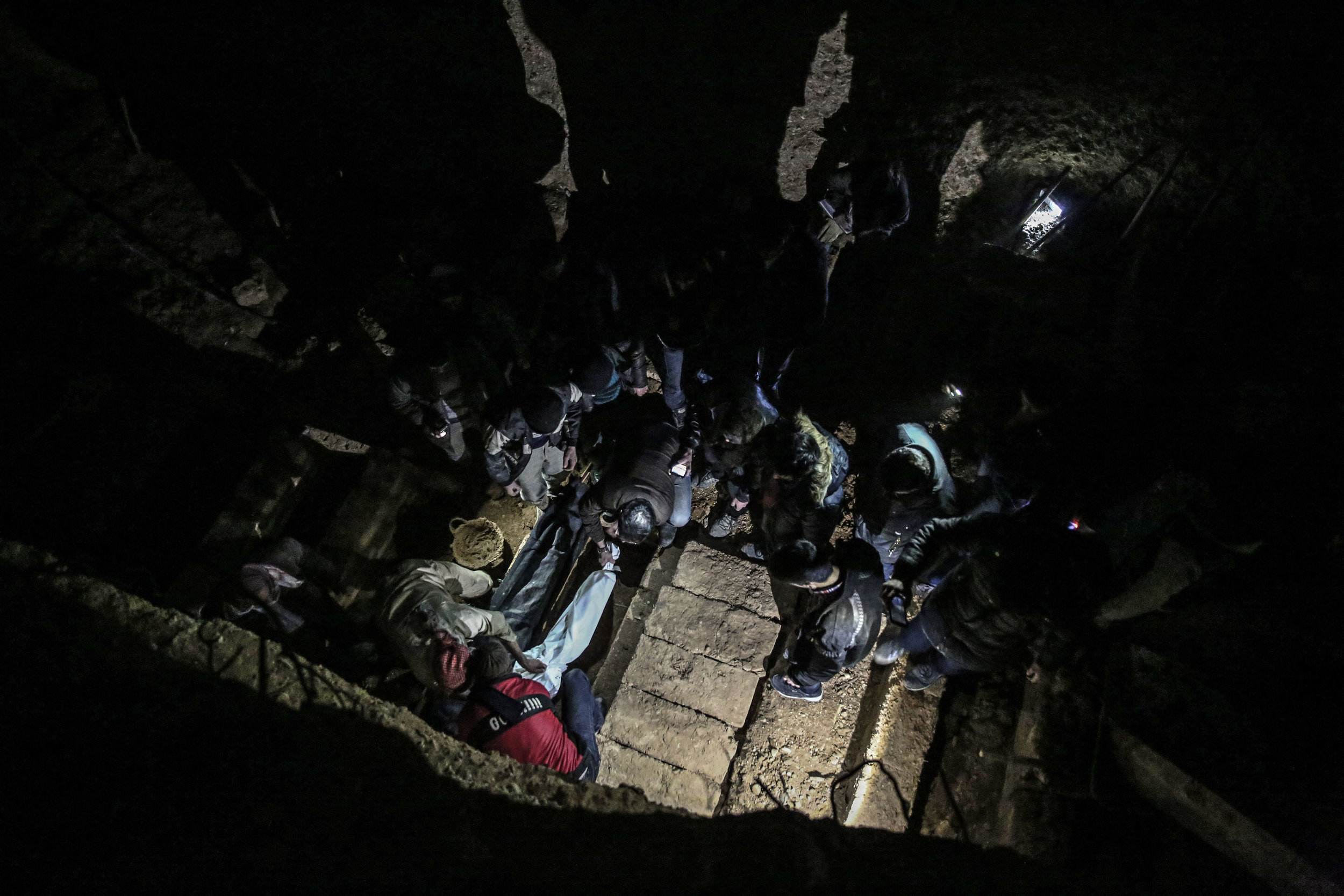 - Men gather to bury the bodies of a family in a layered underground cemetery.