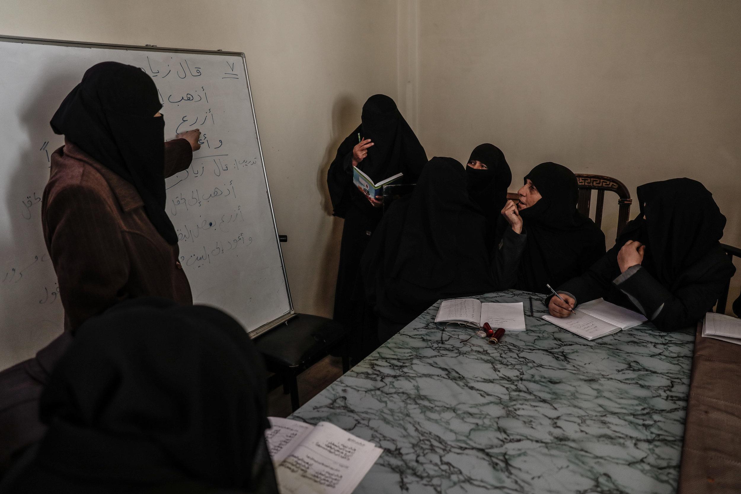 - Umm Mohammed (2-R), attends a literacy class.