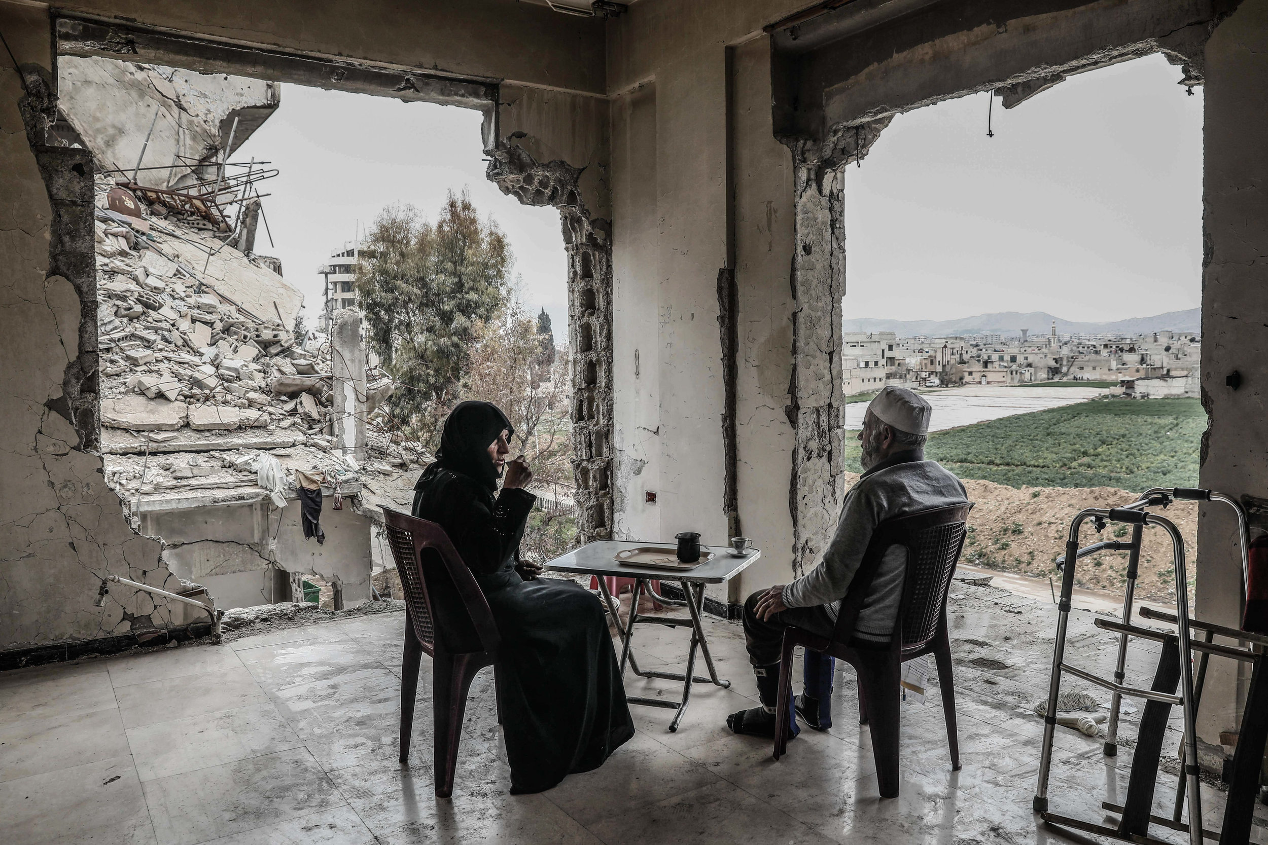 - Umm Mohammed, and her husband drink coffee at their destroyed home.