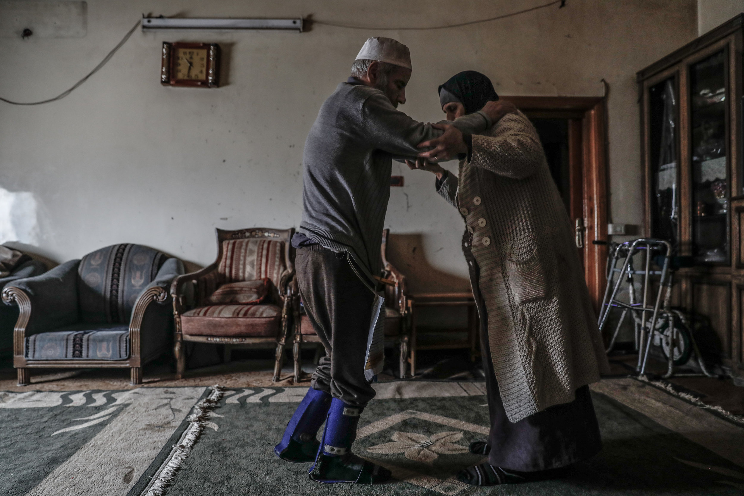 - Umm Mohammed, performs rehabilitation exercises with her war injured husband at their home.