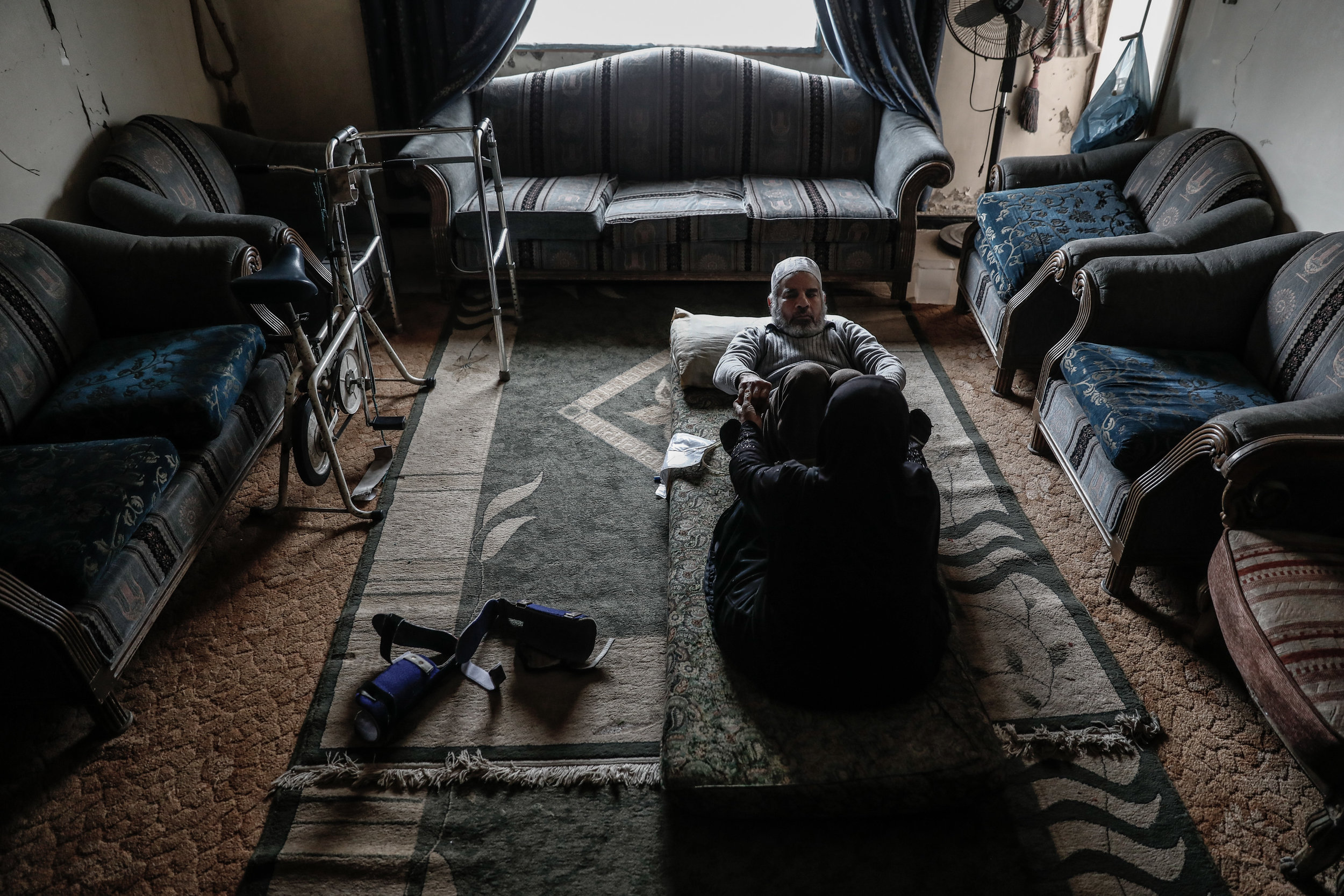 - Umm Mohammed, performs rehabilitation exercises with her war injured husband.