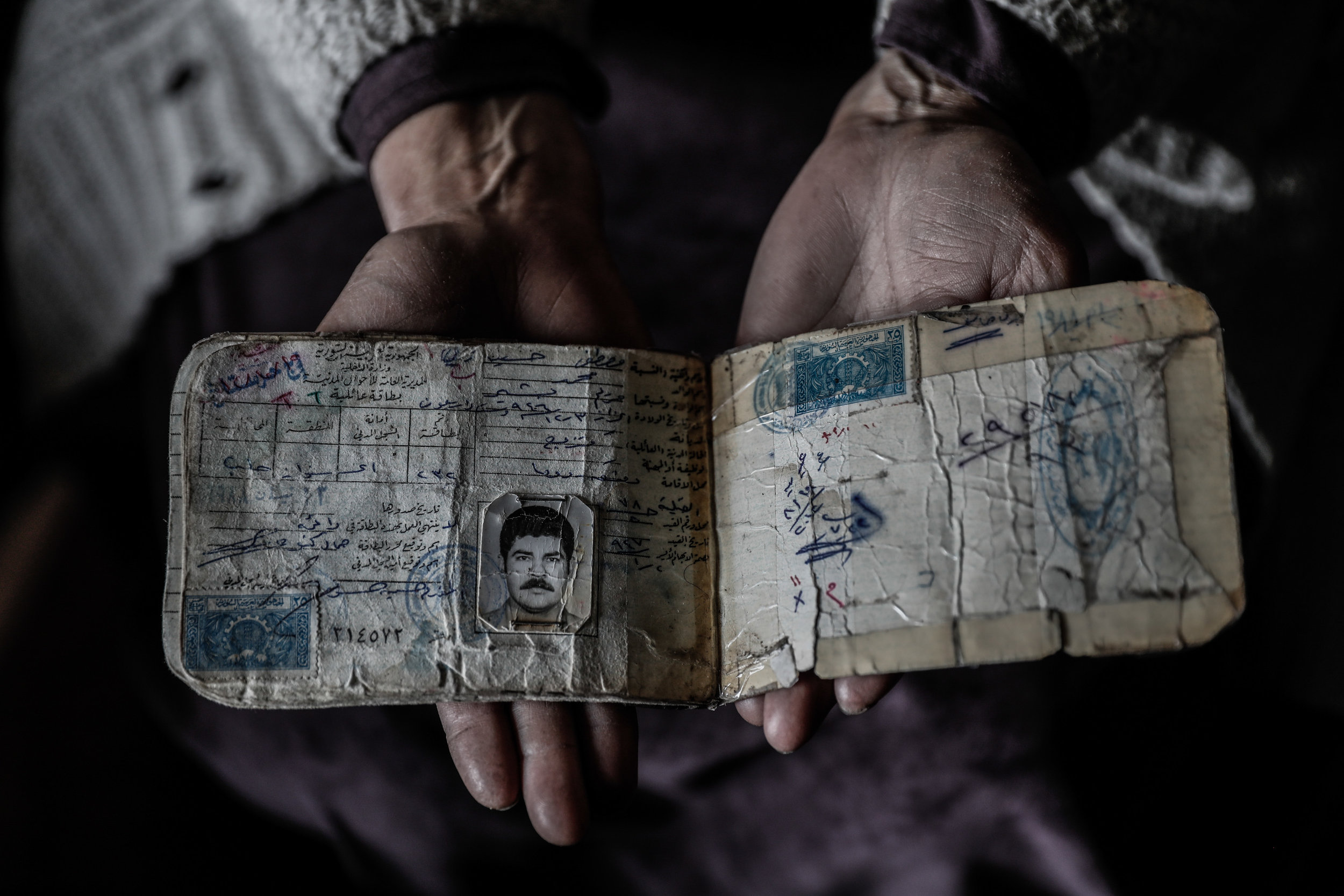 - Umm Mohammed, holds a family ID at her home.
