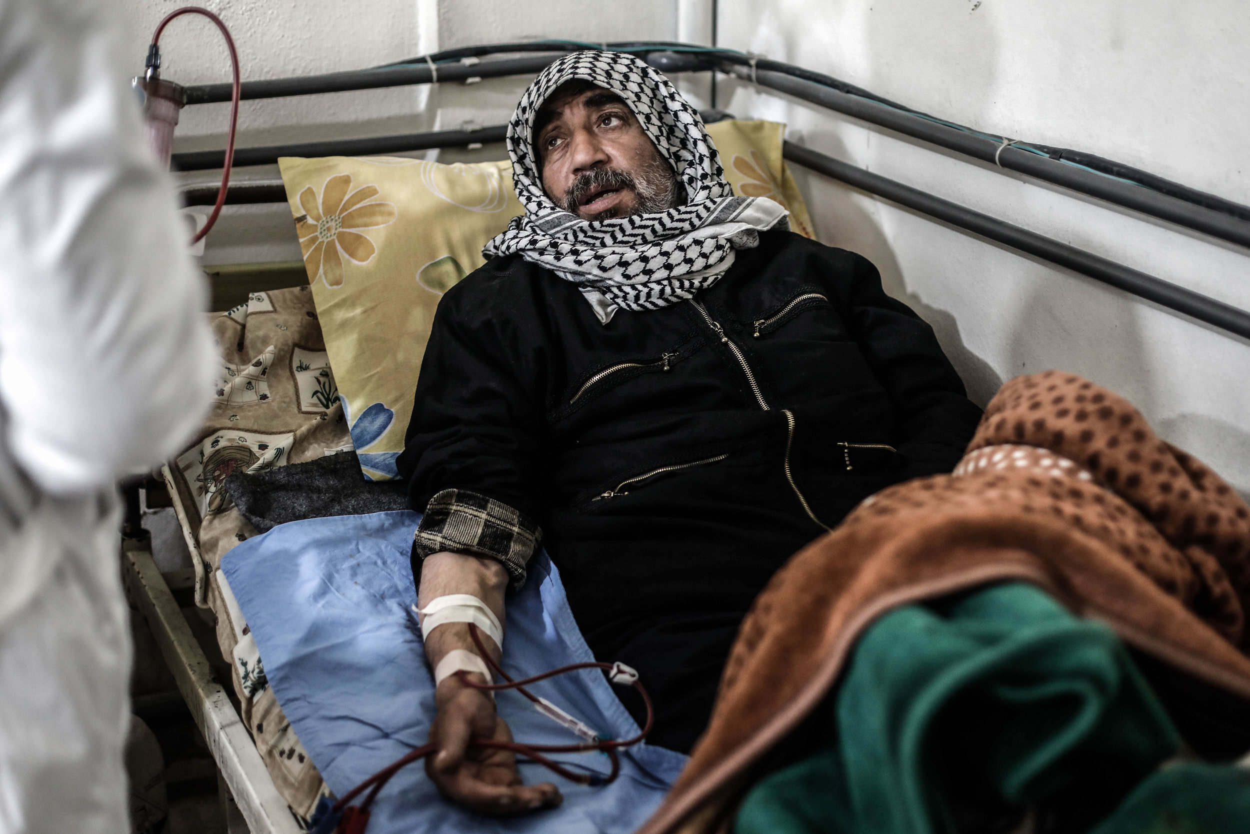 - Syrian Abo Saeed, 60 years old, receives treatment inside a basement-turned-clinic in the city of Douma