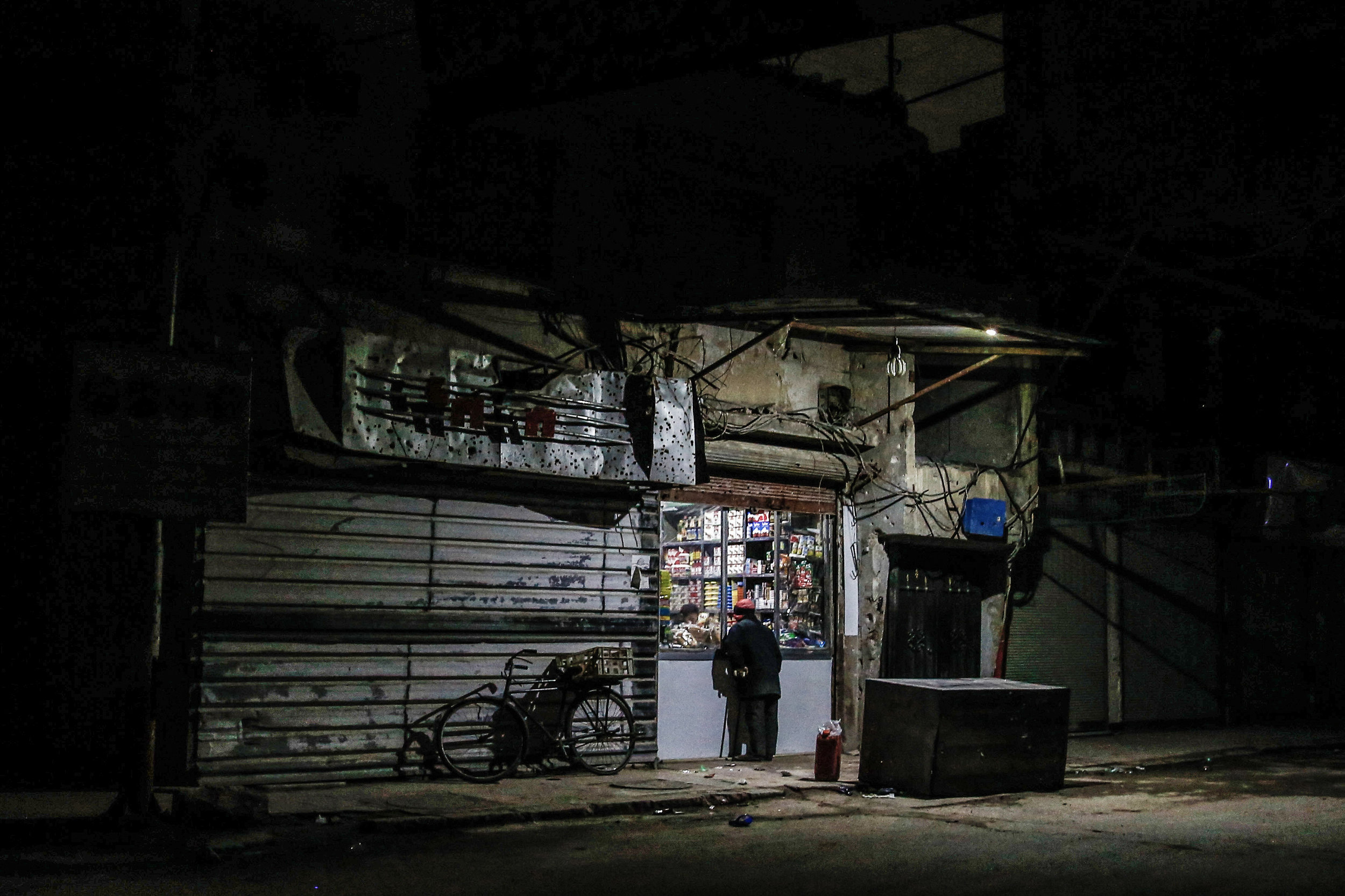 - A man buys groceries from a shop at night in the city of Douma.