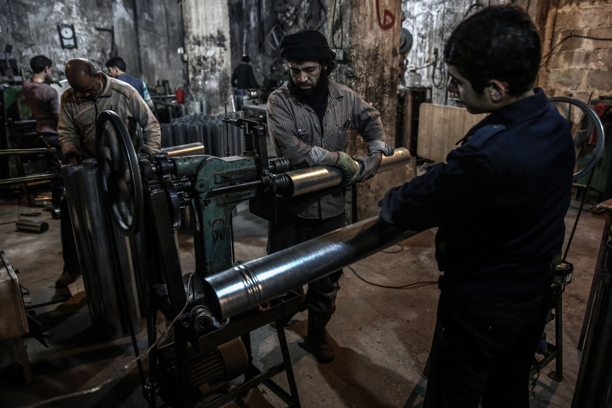 - People work at a factory making wood-burning stoves in the city of Douma.