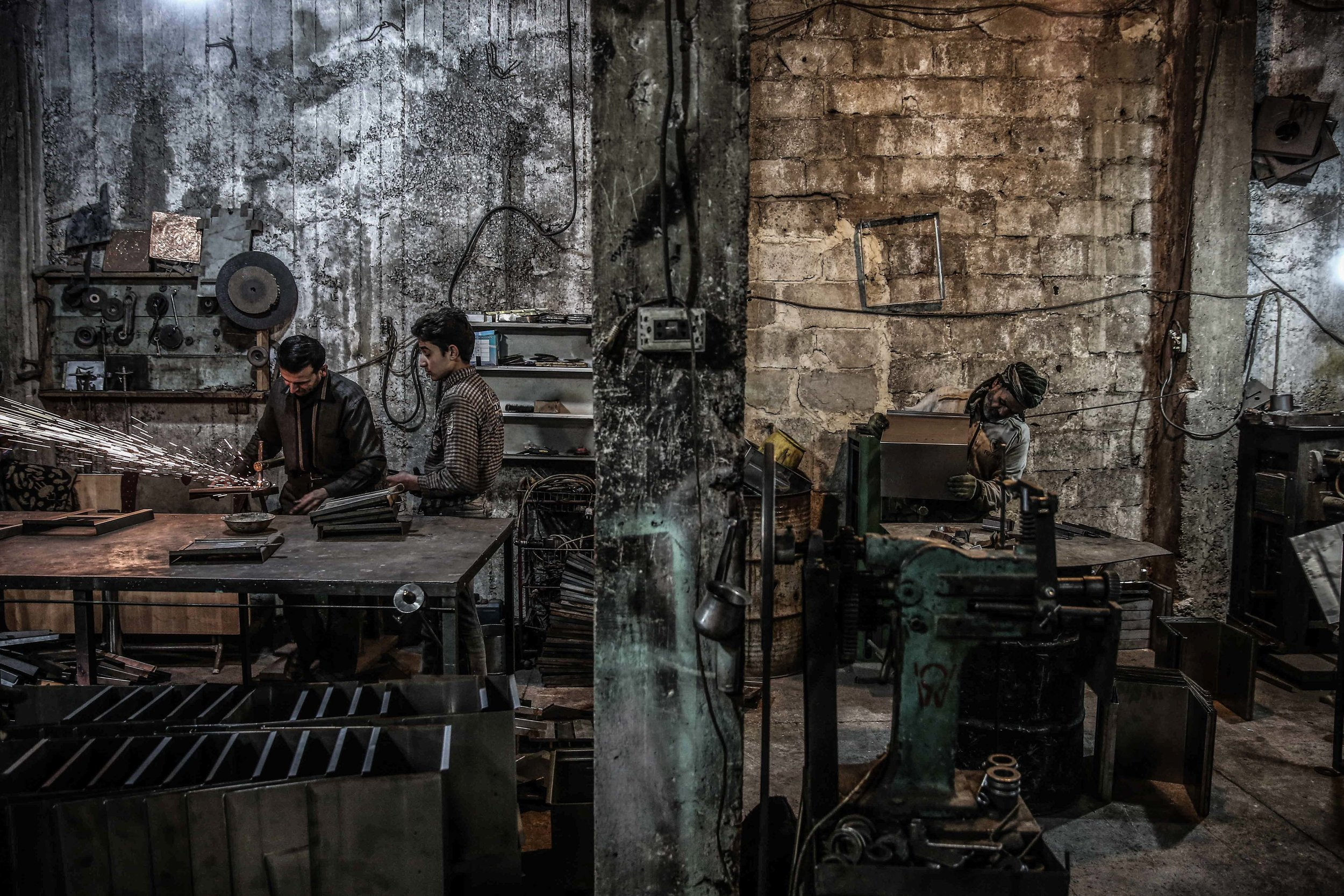 "People work at a factory producing wood-burning stoves, known locally as a ""sobia"", in the city of Douma. As the weather in Douma is getting colder, wood is the most affordable source of heating for residents."