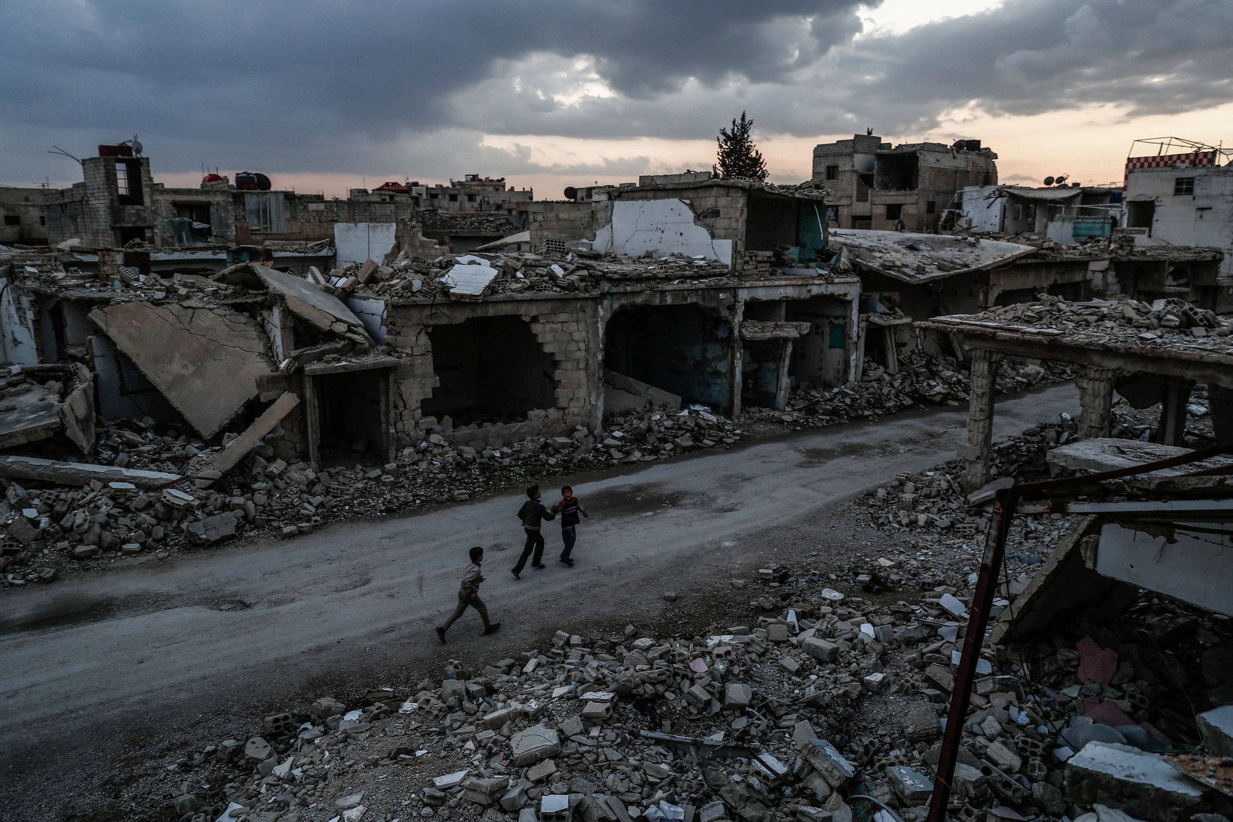 - Children walk past heavily damaged buildings in the city of Douma, on the eastern edges of the capital Damascus on February 27, 2016, on the first day of the landmark ceasefire agreement.
