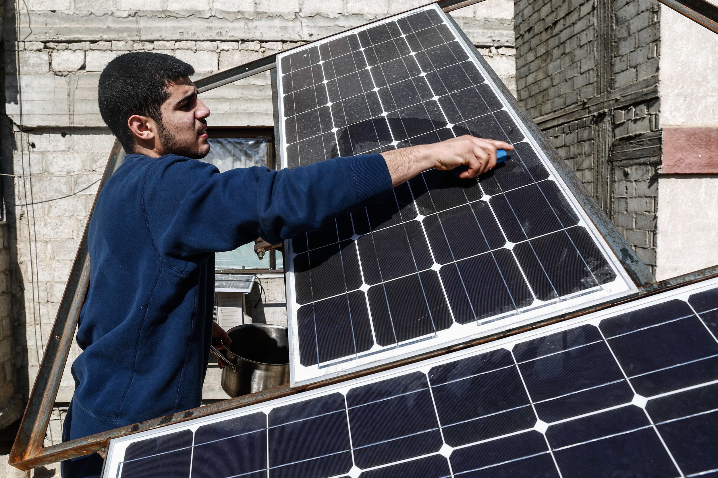 - A man cleans the solar chargers those people started using as an alternative to acquiring electricity power in the Syrian city of Douma.